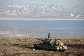 An Israeli soldier stands atop a Merkava tank in the Golan Heights overlooking the Syrian village of Breqa (AFP / FILE PHOTO / Jack Guez)
