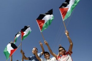 Palestinian children wave their national flag. (AFP PHOTO / GETTY IMAGES / MUSA AL-SHAFER)