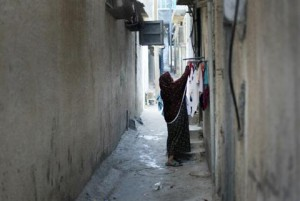 A Palestinian woman hangs laundry outside her house at the Shati Palestinian refugee camp in Gaza City on 3 November. (AFP PHOTO / MAHMUD HAMS )