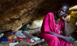 A mother and child rest in a cave in South Kordofan, Sudan. They are among thousands of civilians sheltering from aerial bombing. (AFP / GETTY IMAGES)