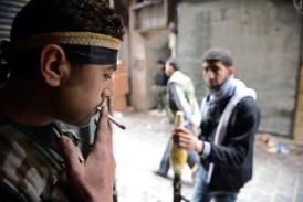A Syrian rebel smokes a cigarette as his comrade stands guard with an RPG. (AFP / Philippe Desmazes)