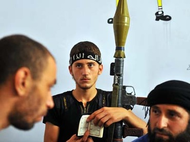 A fighter from the Syrian opposition holds a Koran, Islam's holy book, and a rocket-propelled grenade (RPG). (AFP PHOTO / BULENT KILIC)