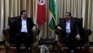Tunisian Foreign Minister Rafik Abdessalem (left) meets with senior Palestinian Hamas member Bassem Naim upon arrival in Rafah through the border crossing between Egypt and the southern Gaza Strip on 17 November. (AFP PHOTO)