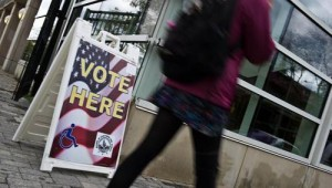 A woman walks past a sign at an early voting centre in Washington on Oct 31, 2012. (AFP PHOTO)