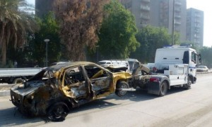 A damaged vehicle is towed away following a car bomb near Firdos Square in Baghdad on November 14 (AFP, Sabah Arar)