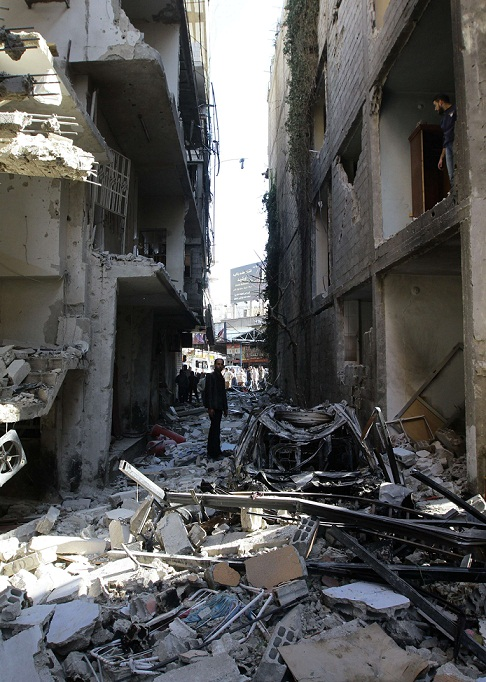 Syrian men inspect an alley packed with debris in the aftermath of a car bomb explosion in Jaramana, a mainly Christian and Druze suburb of Damascus, on 28 November. (AFP PHOTO / LOUAI BESHARA)