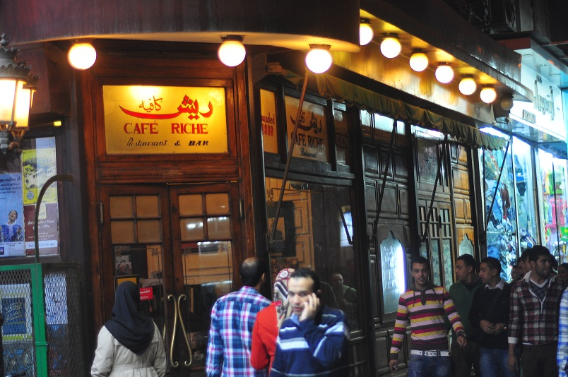 Pedestrians pass by the alluring exterior of Cafe Riche Hassan Ibrahim