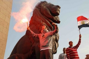 A man burns a flare while stood on the Qasr Al-Nile bridge, passed by a march to Tahrir Square to protest against President Morsy's perceived consolidation of power. (DNE/ Hassan Ibrahim)