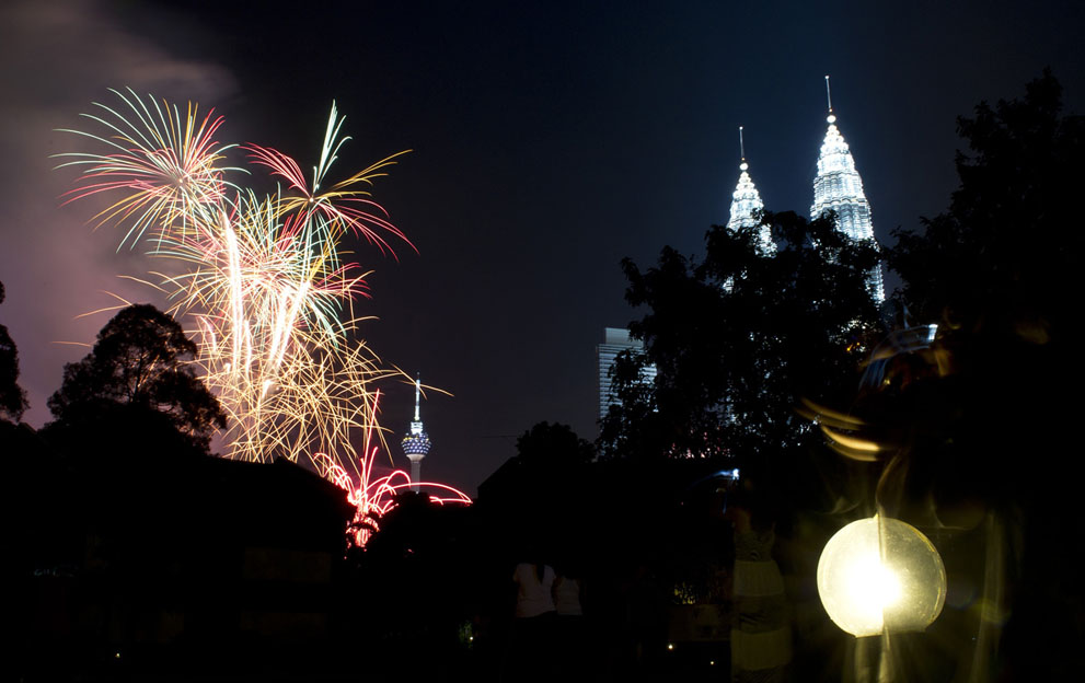 Residents watch fireworks displays above the Malaysia's iconic landmarks, the Twin Towers, during the new year celebrations in Kuala Lumpur, on January 1, 2012. Saeed Khan/AFP/Getty Images