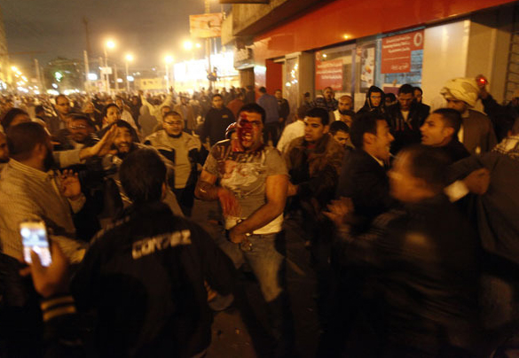An injured Egyptian opposition protester (centre) runs as he is surrounded by members of the Muslim Brotherhood and supporters of President Morsy during clashes with anti-Morsy demonstrators on the road leading to the Egyptian presidential palace on 5 December (AFP Photo / Mahmoud Khaled)