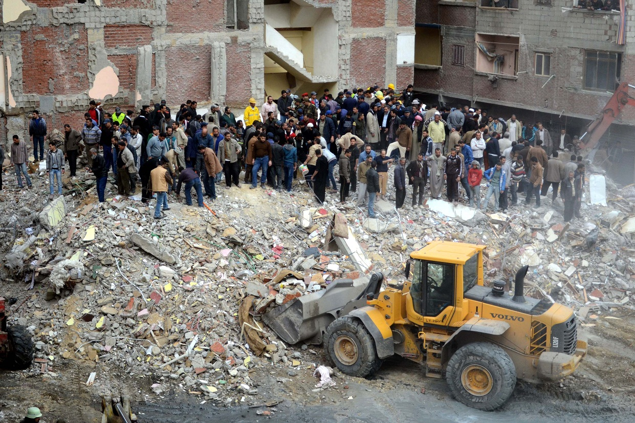 Egyptian civilians and emergency services sift through the rubble of a building housing 24 families in the Maamura district of Alexandria which collapsed in the early hours on January 16, 2013. AFP PHOTO/STR
