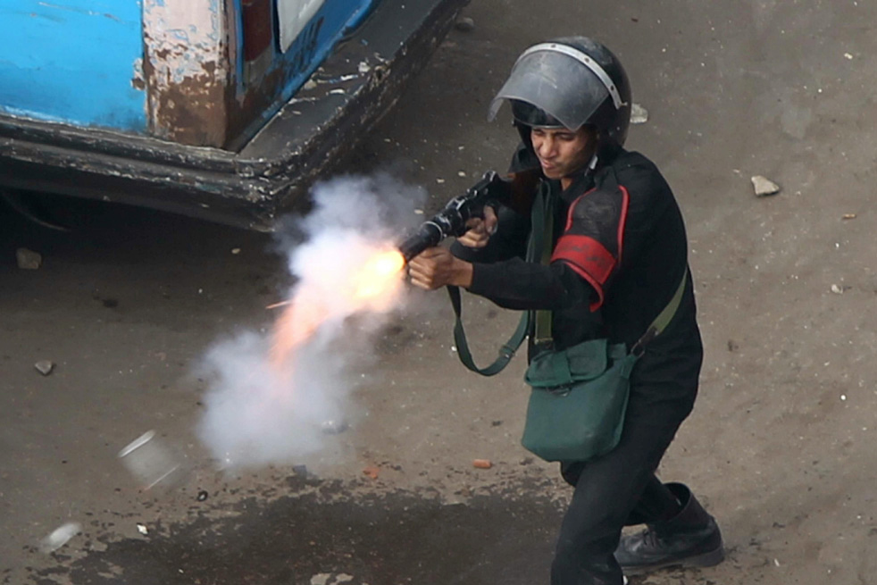 An Egyptian police officer fire tear gas at demonstrators in Cairo AFP Photo / Khaled Desouki