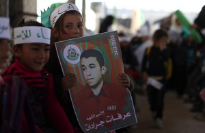 A Palestinian girl carries a poster of Arafat Jaradat, who died in an Israeli prison, during a protest at Erez border crossing between Israel and the northern Gaza Strip on (AFP Photo)