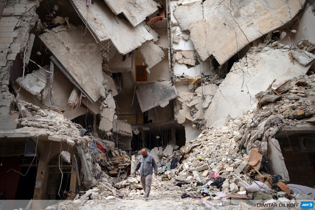 A man walks amid a ruined building in the northern Syrian city of Aleppo (AFP Photo)