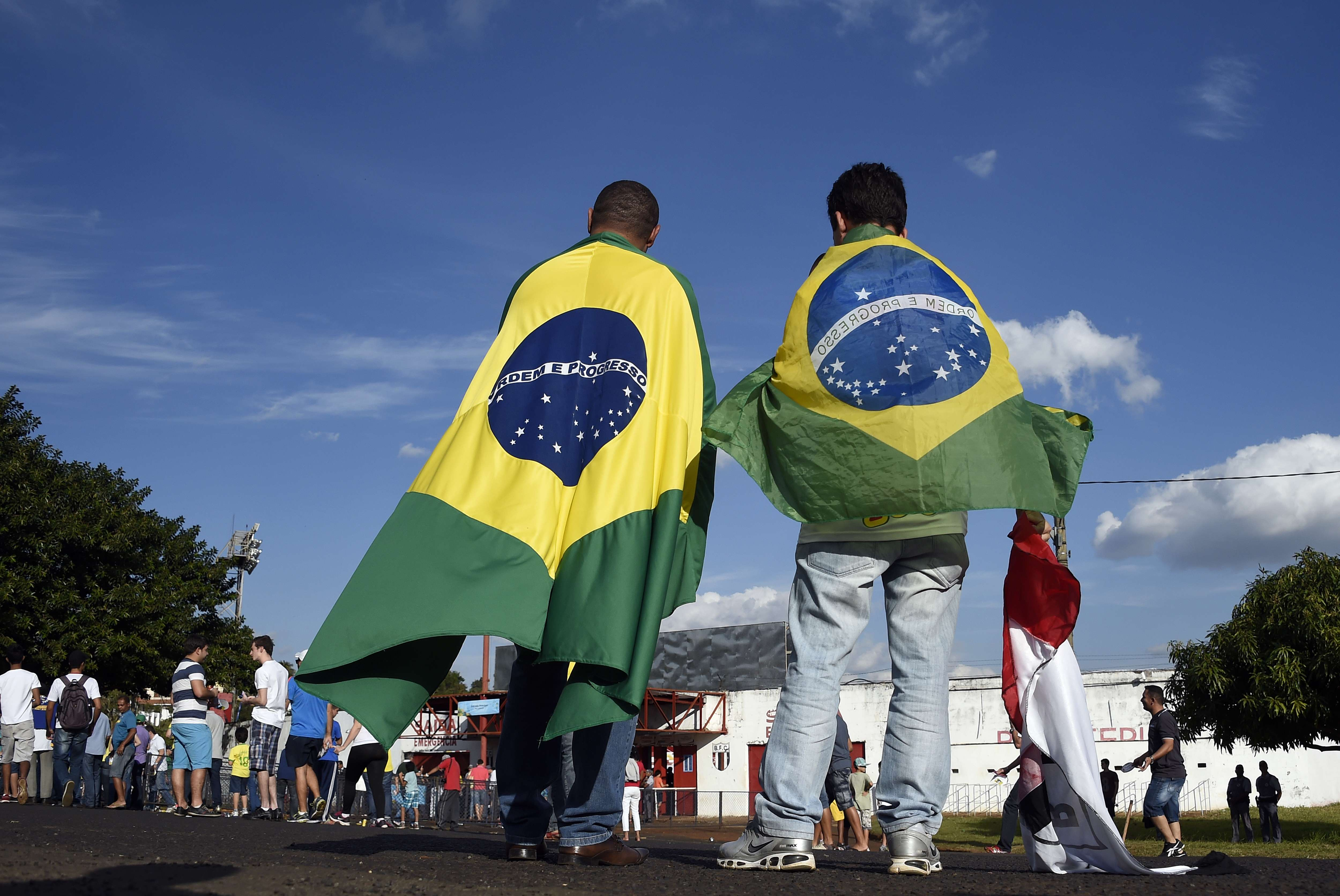 People wearing Brazilian flags arrive at the Santa Cruz Stadium in Ribeirao Prato to attend a France's national football team training session on June 10, 2014, a few days prior to the start of the 2014 FIFA World Cup in Brazil.      (AFP PHOTO / FRANCK FIFE)