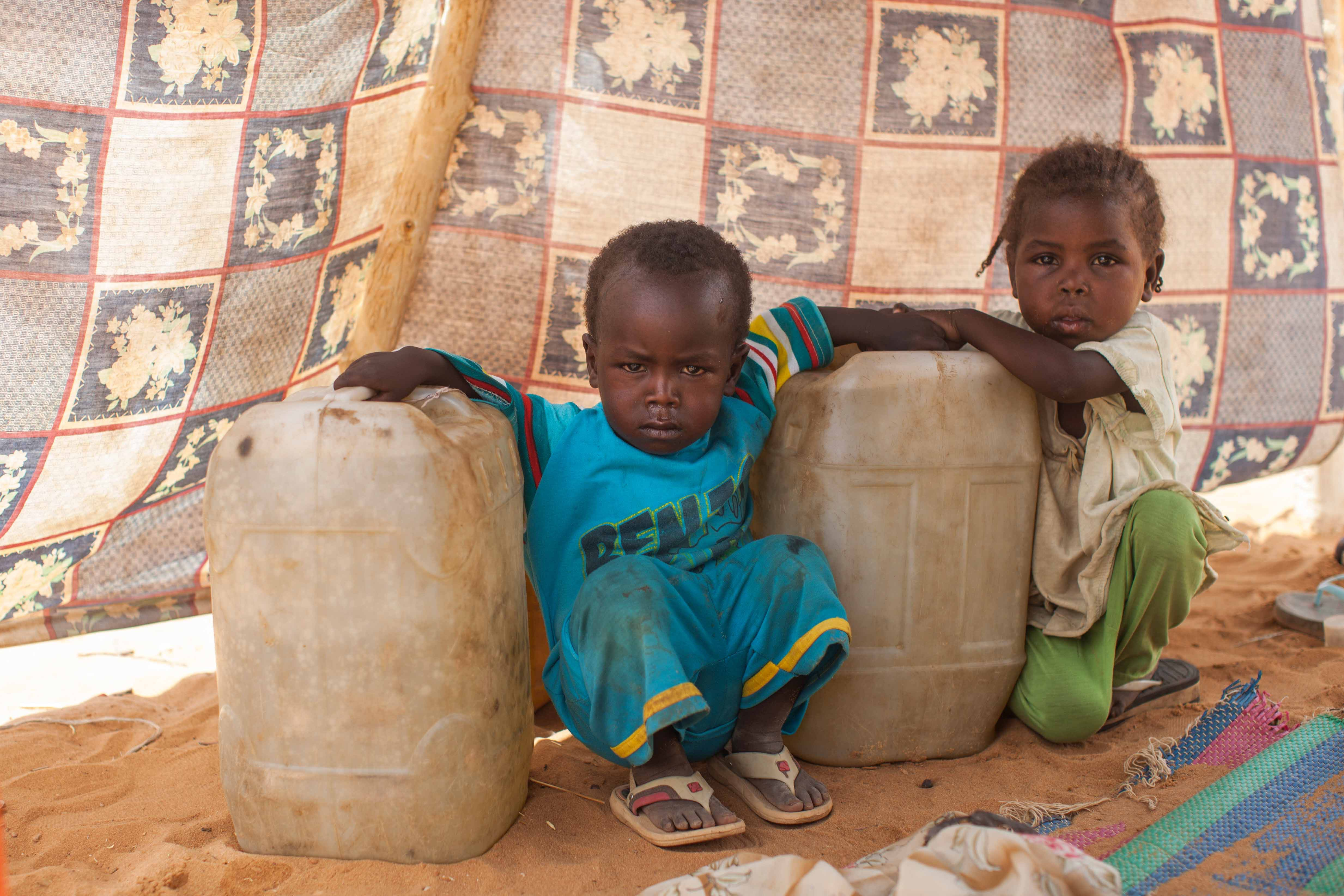 A handout picture released by the United Nations-African Union Mission in Darfur (UNAMID) on June 11, 2014 shows a two children photographed next to water jerry cans inside their shelter in a new settlement in Zam Zam camp for Internally Displaced People (IDP), North Darfur. Thousands of people, mostly women, children and the elderly, have sought refuge in the Zam Zam IDP camp,  following an armed militia attack on their villages more than three months ago. Many of the recently displaced hail from different villages around Tawila, Korma and Tina in North Darfur as well as Khor Abeche in South Darfur. The displaced community continues to request for basic services such as water, food, healthcare services and shelter.   (AFP PHOTO/UNAMID/ALBERT GONZALEZ FARRAN )