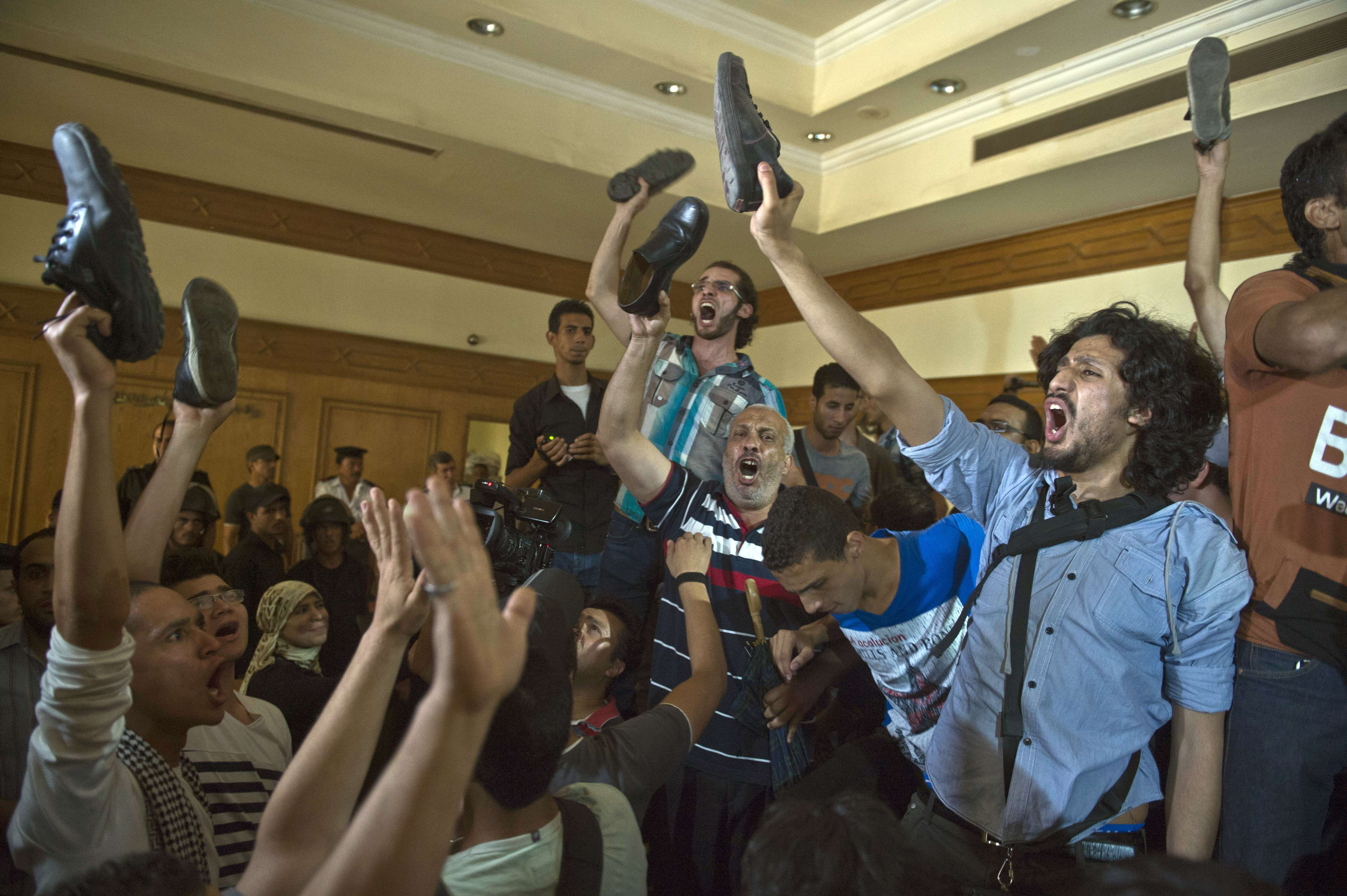 Egyptian relatives and friends of political activist Ahmed Douma hold up a shoe as they react at the end of his trial in Cairo, on June 3, 2013, on charges of insulting President Mohamed Morsi. (AFP Photo)