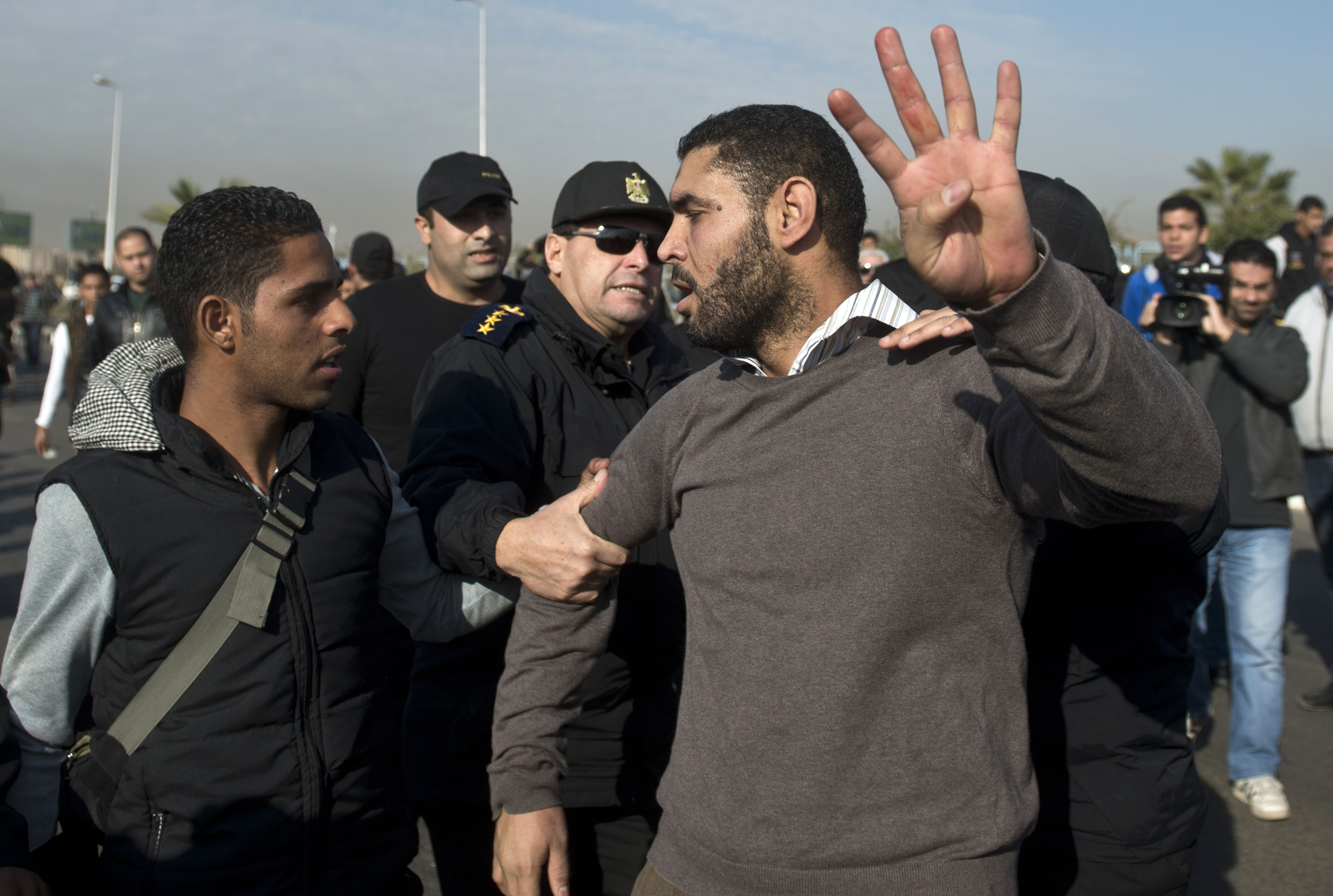 "A supporter of Muslim Brotherhood ousted president Mohamed Morsi, flashing the ""Rabaa"" sign, is arrested by Egyptian policemen outside the police academy where takes place the second hearing in his murder trial on January 8, 2014 in Cairo. Toppled by the military in July, Morsi is charged with inciting the killings of opposition activists in clashes outside the presidential palace in December 2012. ( AFP PHOTO / KHALED DESOUKI)"