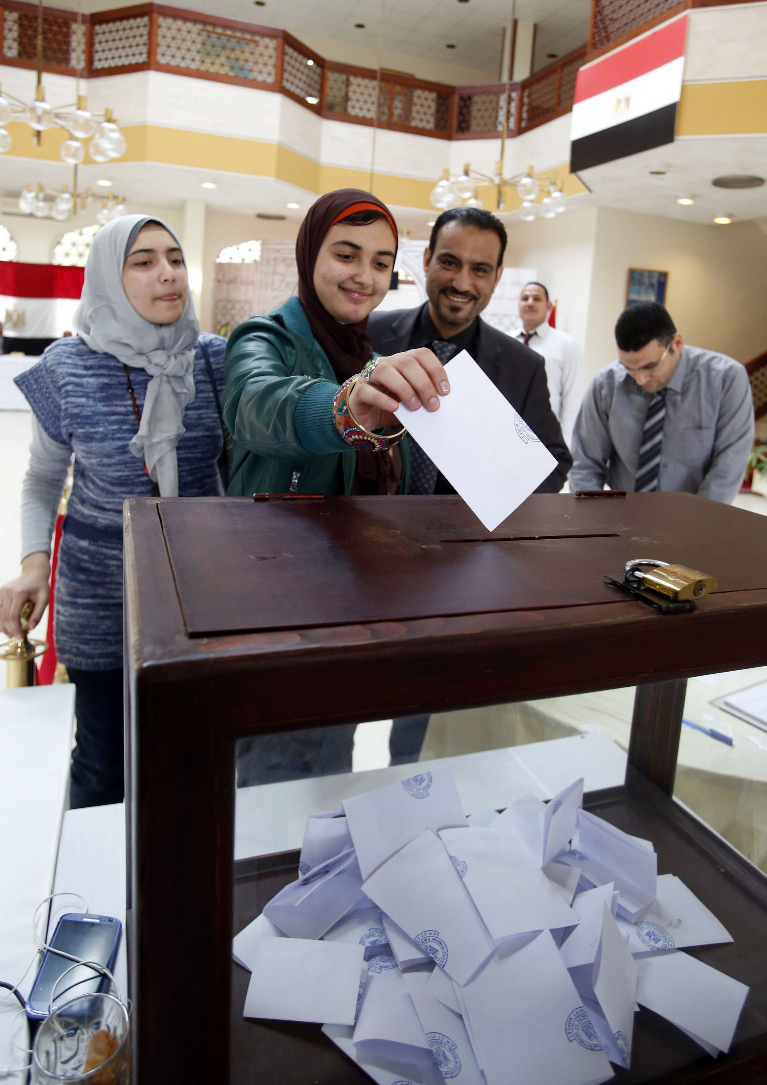 An Egyptian woman living in Oman casts her vote on a divisive draft constitution in Egypt at the Egyptian embassy in the Gulf sultanate's capital Muscat on January 8, 2014. Islamist supporters of deposed president Mohamed Morsi have called for a boycott of the January 14-15 vote on a new constitution drawn up by the interim authorities since his July overthrow by the army.  (AFP PHOTO/MOHAMMED  MAHJOUB)