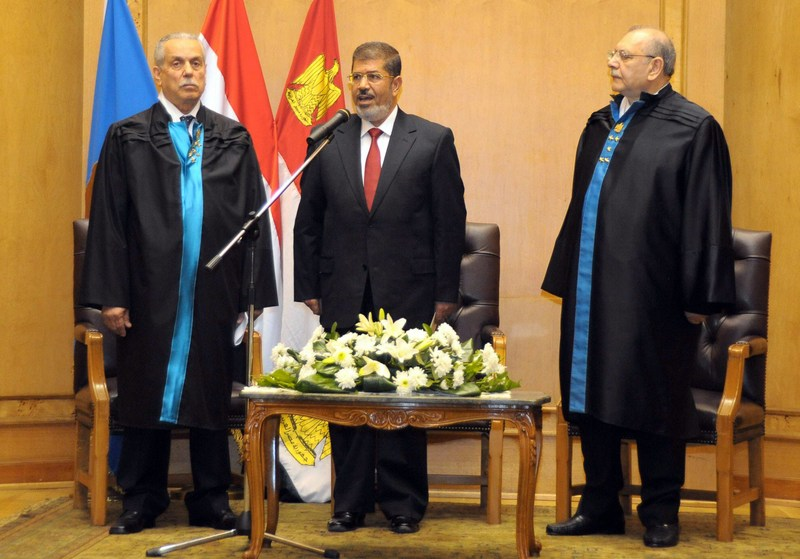 President Mohamed Morsi (C) stands next to Faruq Sultan (L), head of the presidential election commission as he takes the oath of office during his swearing-in ceremony at the Constitutional Court in Cairo on June 30, 2012 to become the country's first freely elected president since Hosni Mubarak's overthrow (AFP File Photo)