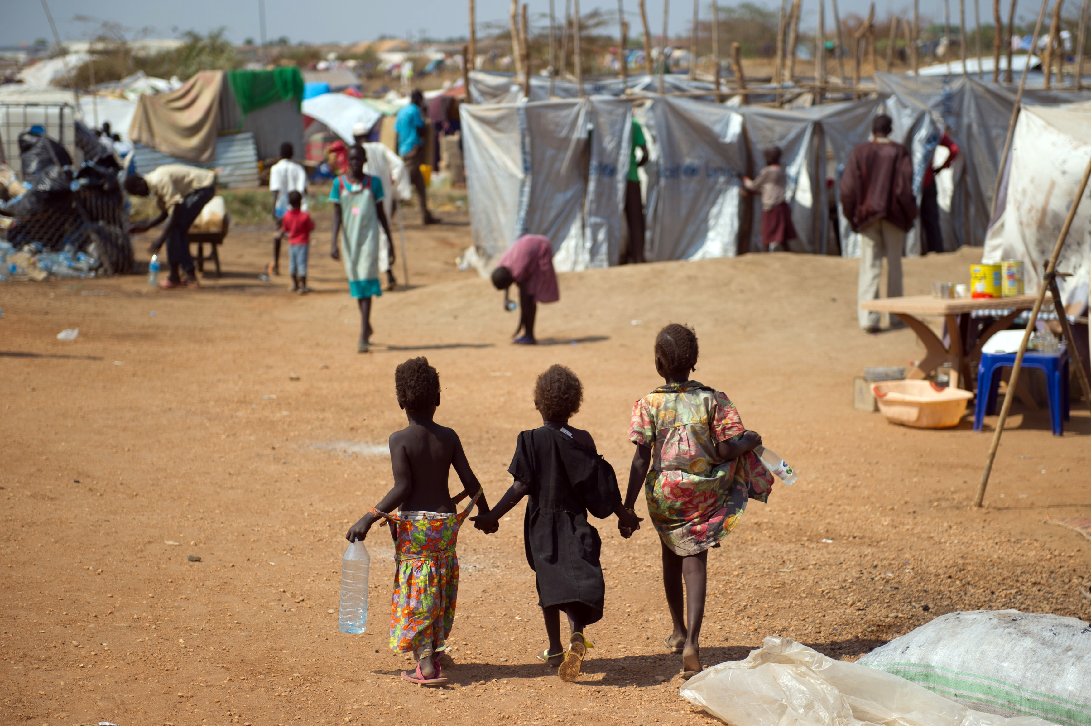 Three children walk through a spontaneous camp for internally displaced persons at the United Nations Mission to South Sudan (UNMISS) base in Juba,  on January 9, 2014. Over 17,000 people are living at the base, with new arrivals every day, due to ongoing conflict in the world's youngest nation.  (AFP PHOTO/PHIL MOORE)