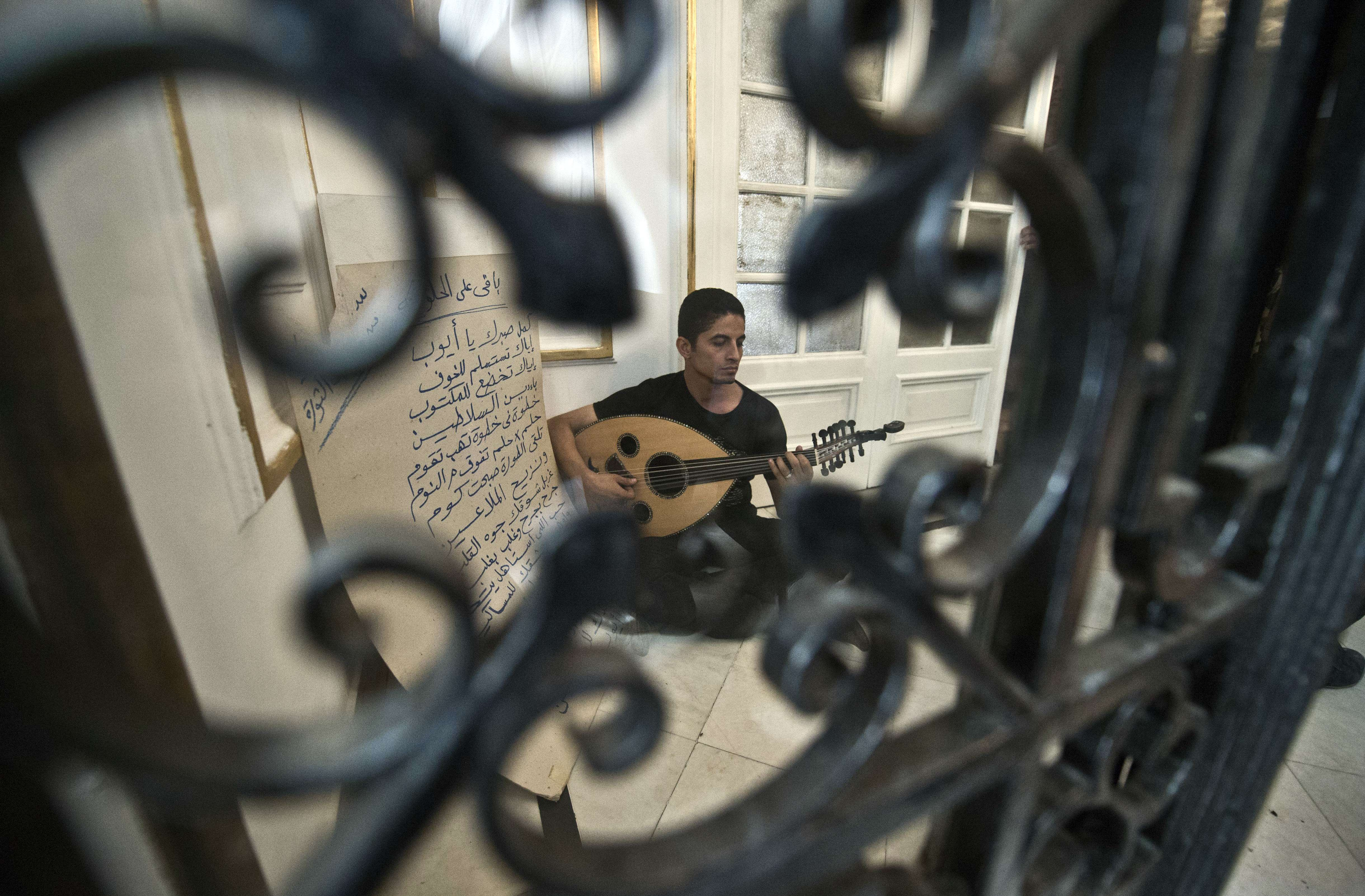 An Egyptian artist plays the Oud as demonstrators perform a sit-in at the office of culture minister, Alaa Abdelfattah, in Cairo on June 6, 2013, calling for his resignation. (AFP Photo)