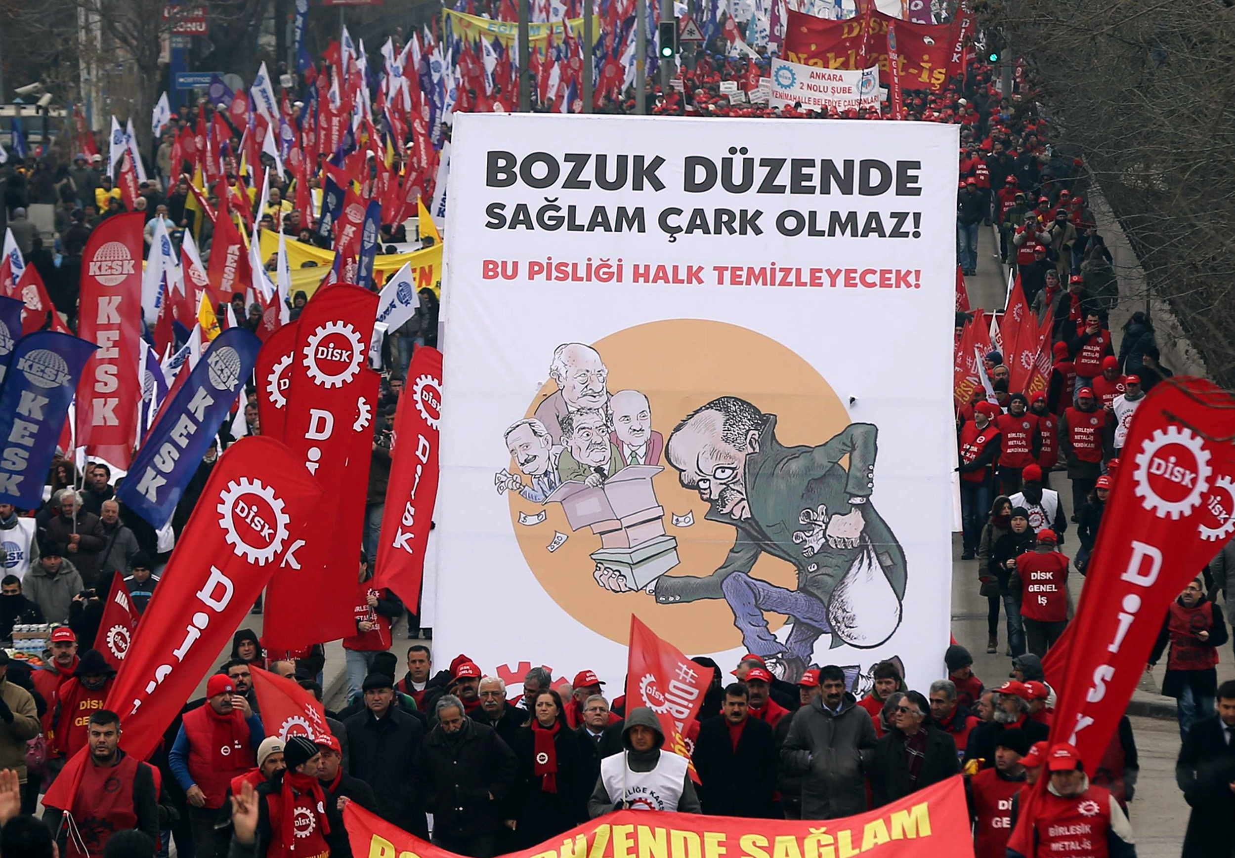 """Protesters hold a placard with a cartoon depicting Turkish Prime Minister Recep Tayyip Erdogan and his three cabinet ministers who resigned under a huge graft scandal during an anti-corruption protest in Ankara on January 11, 2014. Tens of thousands of Turkish demonstrators took to the streets in capital Ankara on January 11 in protest against Prime Minister Recep Tayyip Erdogan's government, which has been rocked by a vast corruption probe. Placard reads : """"No one is clean if the whole system is corrupt"""".   (AFP PHOTO / ADEM ALTAN)"""