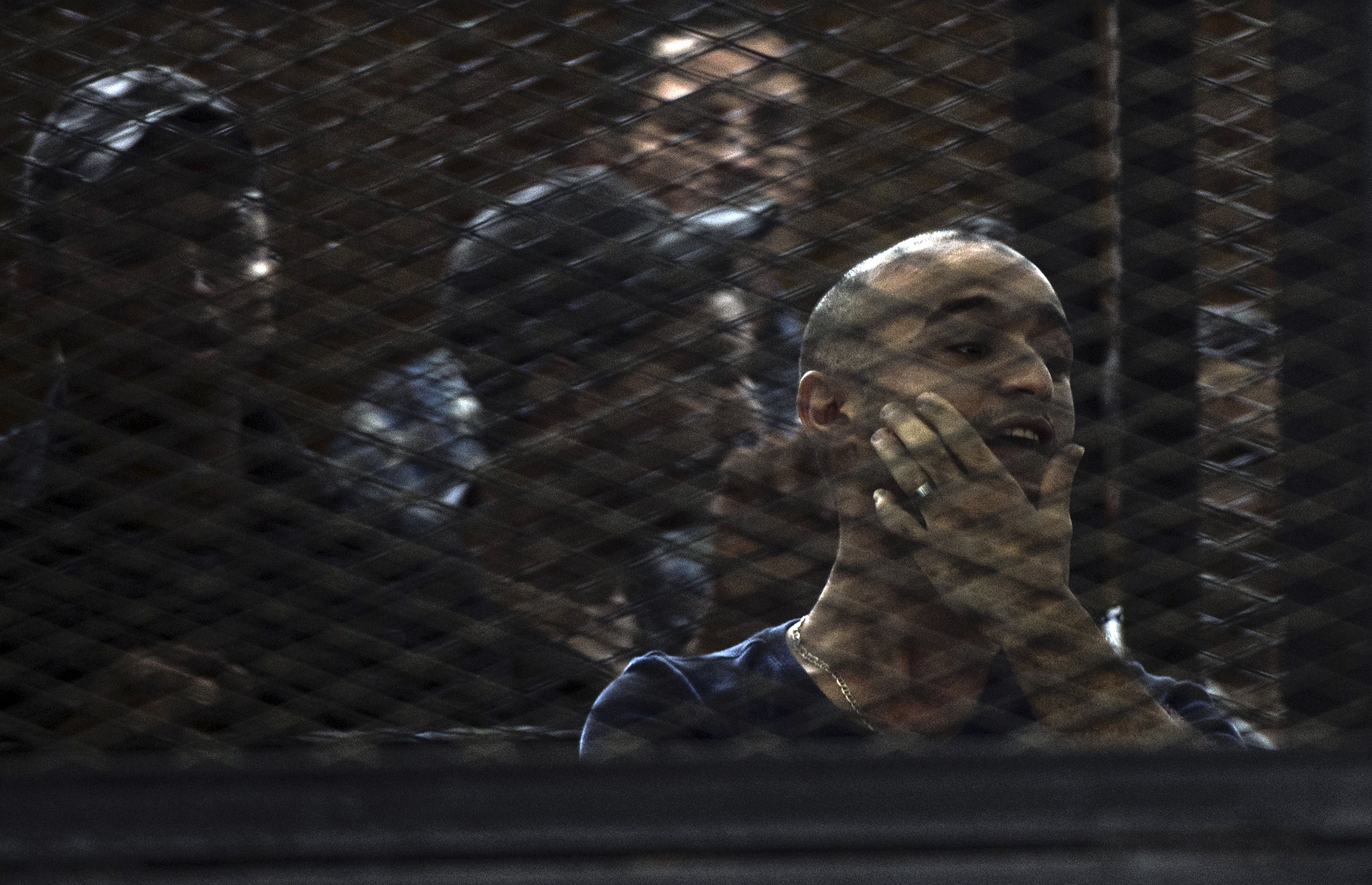 Egyptian political activist Ahmed Doma gestures behind the bars of the accused dock during his trial on charges of taking part in an unauthorized protest on June 15, 2014 in Cairo, Egypt. Ahmed Doma and 268 others are standing trial for alleged violence during clashes with security forces outside the Council of ministers headquarters in December 2011.  (AFP PHOTO / KHALED DESOUKI)