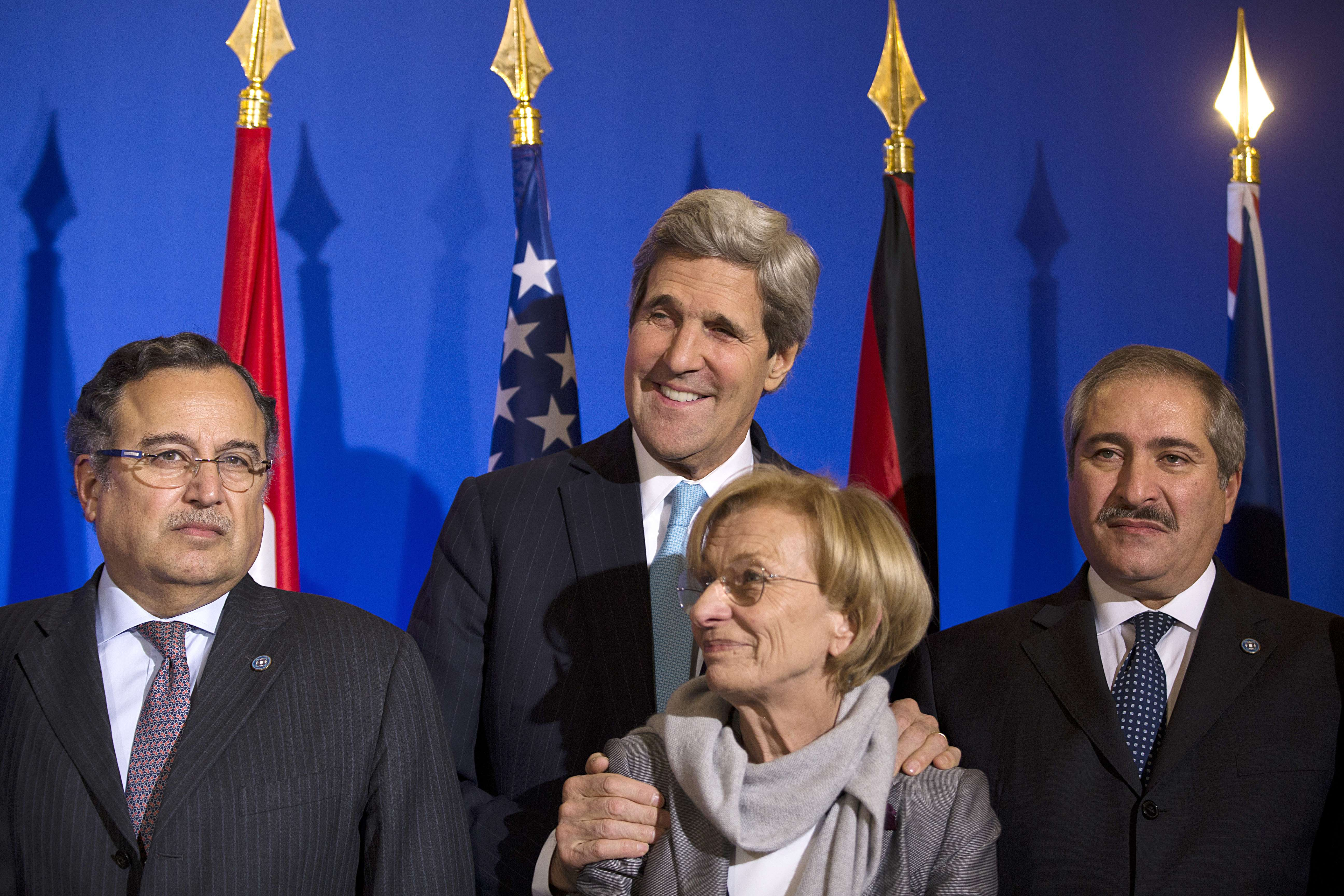 """US Secretary of State John Kerry (C,background) flanked by counterparts Emma Bonino of Italy (C), Nabil Fahmy of Egypt (L) and Marwan Moasher of Jordan (R) prepare to pose for a family picture at the Quai d'Orsay, the French Foreign ministry in Paris on January 12, 2014) after the conference of """"Friends of Syria"""". The group met with leaders of the mainstream opposition to President Bashar al-Assad ahead of peace talks due later this month. The Coalition of eleven countries has yet to decide whether it will take part in UN-backed peace talks aimed at negotiating an end to a conflict that has left more than 130,000 people dead and millions displaced since it erupted in March 2011.  (AFP PHOTO / JOEL SAGET)"""