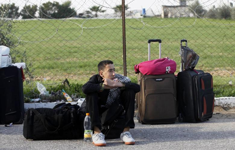 A Palestinian youth waits near luggage, hoping to cross into Egypt, at the Rafah crossing between Egypt and the southern Gaza Strip on January 21, 2014.  ( AFP Photo/Said Khatib)