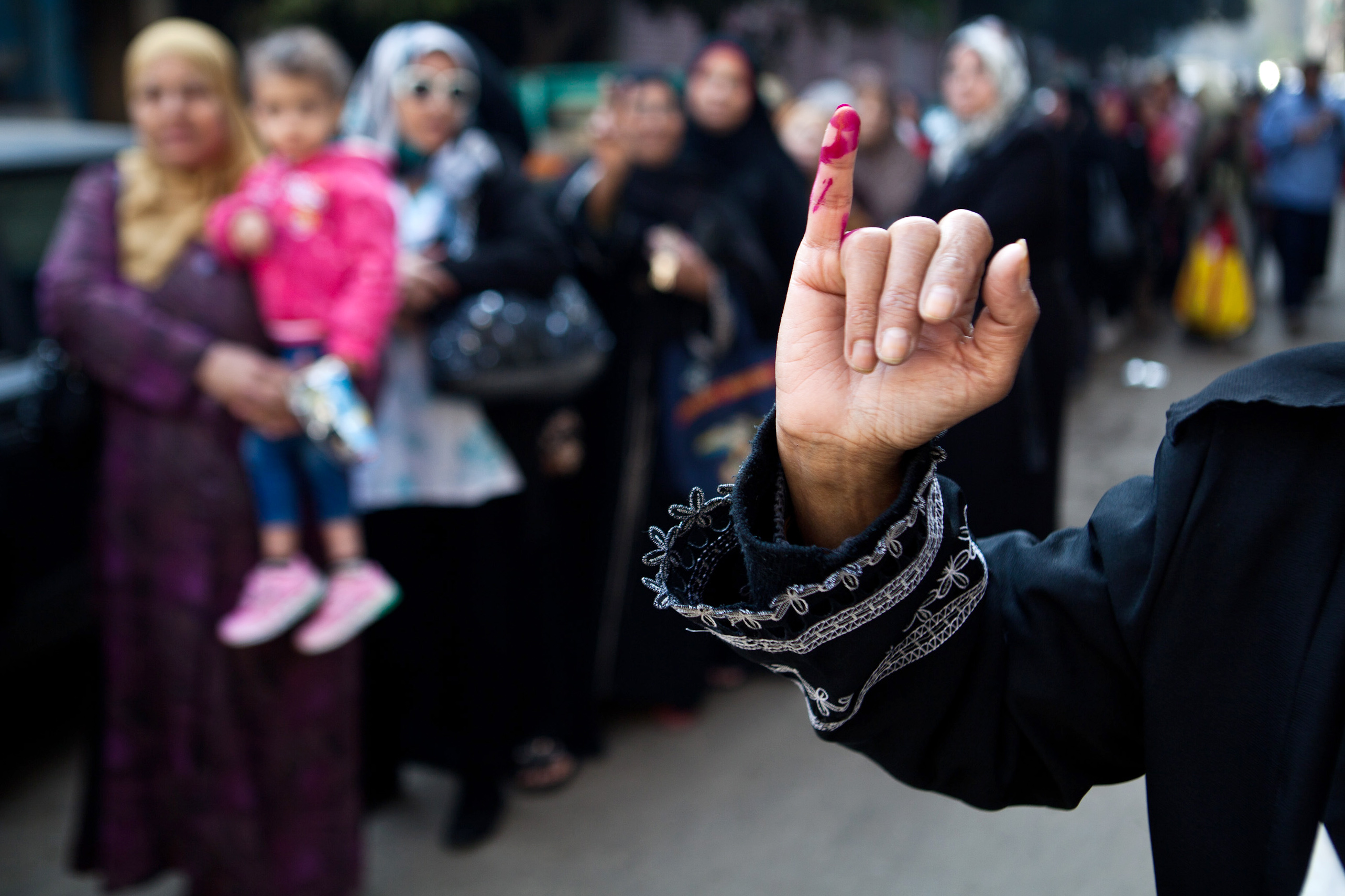 A woman shows her ink-marked finger as she leaves a polling centre after voting on a new constitution on January 14, 2014 in Mounira, a district of Cairo. Egyptians vote on a new constitution amid high security in a referendum likely to prompt a presidential bid by the army chief who overthrew Islamist president Mohamed Morsi.     (AFP PHOTO / VIRGINIE NGUYEN HOANG)
