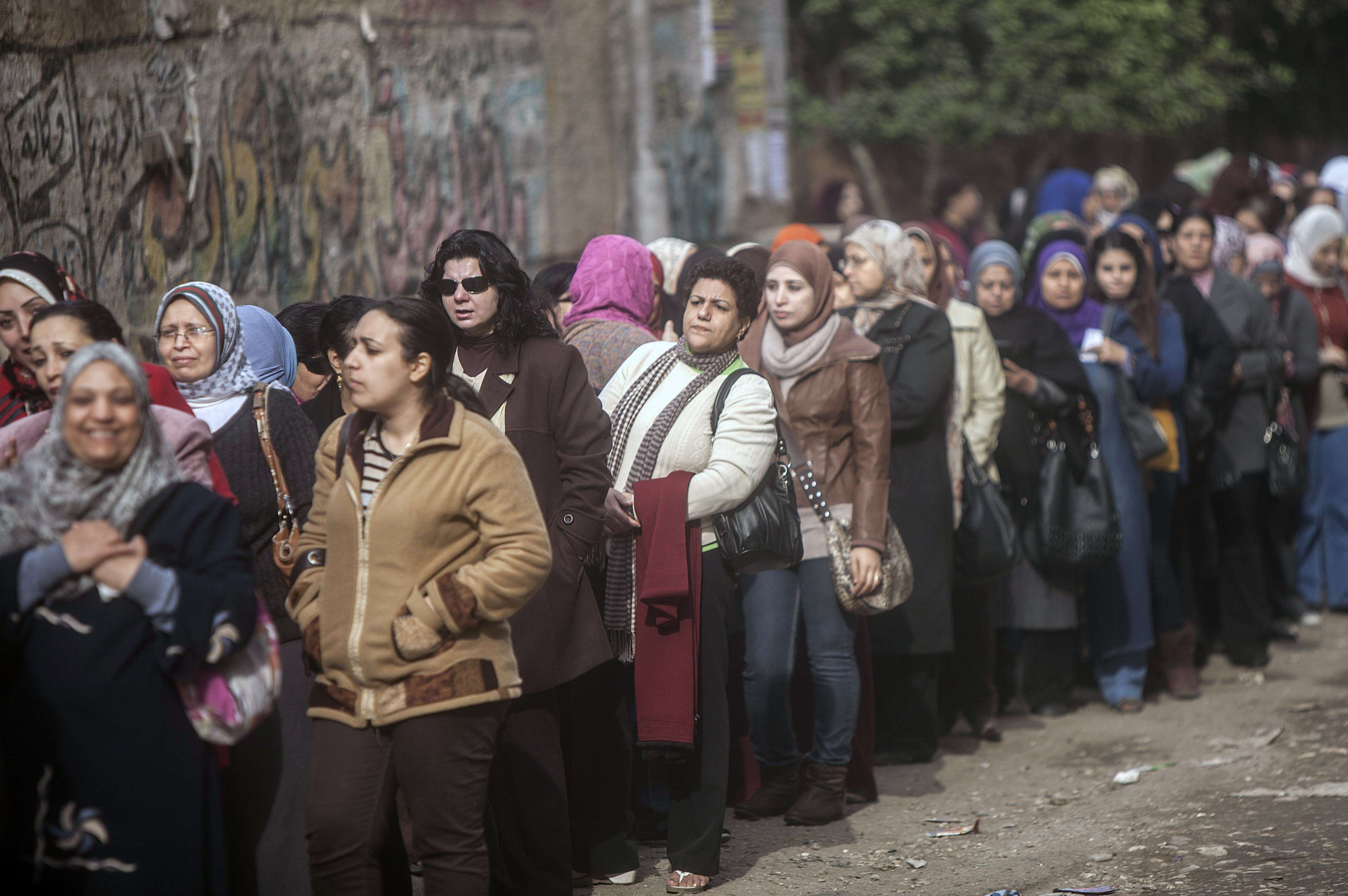 Egyptian women queue up to cast their vote on a new constitution in Al-Haram in the southern Cairo Giza district on January 14, 2014. The military-installed government implored voters to turn out en masse to ratify the constitution, with the country's lingering polarisation underscored by the explosion of a small bomb in Cairo that caused no injuries.  (AFP PHOTO / MAHMOUD KHALED)