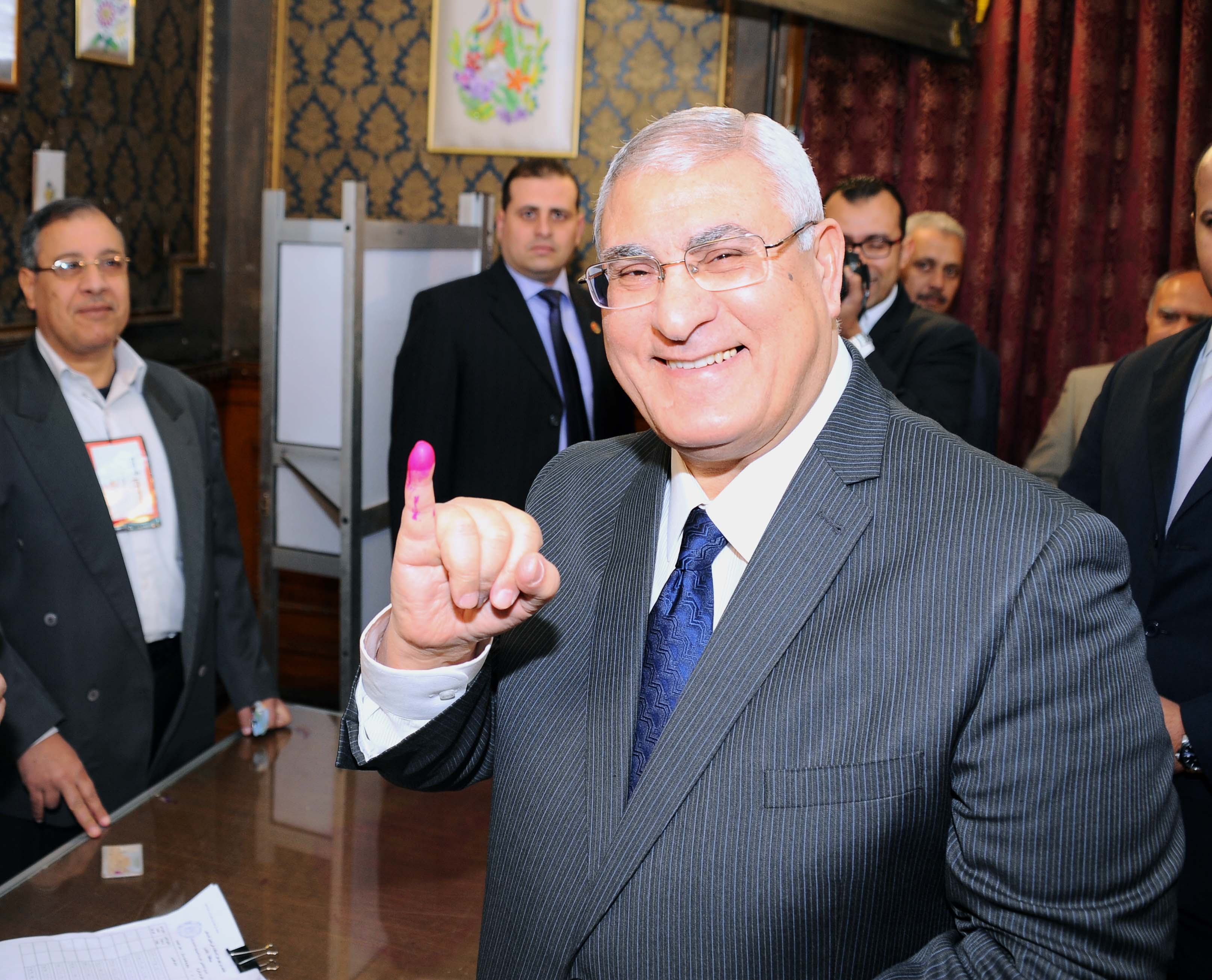 A handout picture released by Egyptian presidency shows Egypt's interim president Adly Mansour showing his ink-stained finger after voting on a new constitution outside a polling station in Cairo on 14 January 2014.