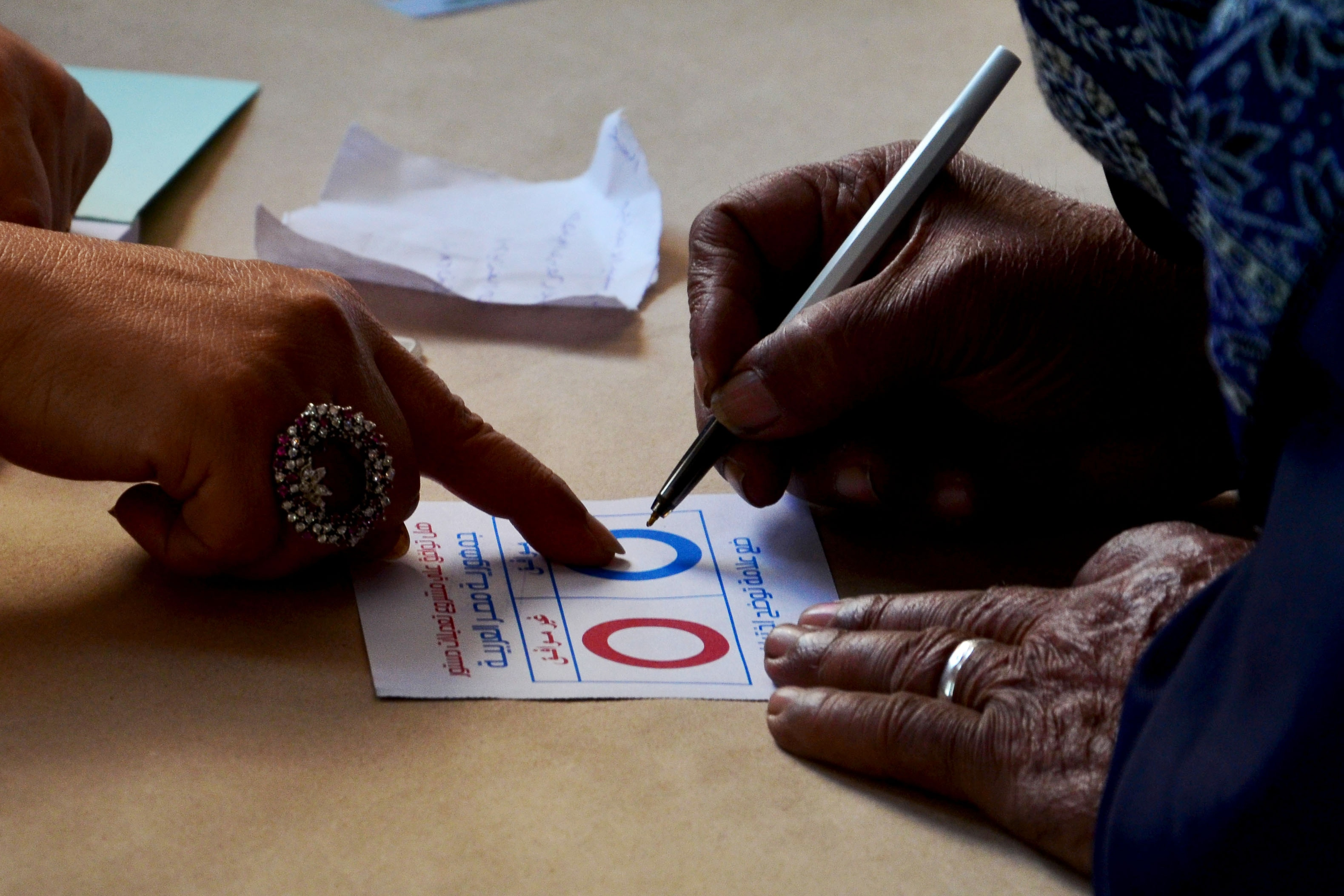 A woman fills in a ballot paper as she votes on a new constitution at a polling station in the coastal Egyptian city of Alexandria on January 14, 2014 during the vote.  (AFP PHOTO / MOHAMED ABDELAZIZ)