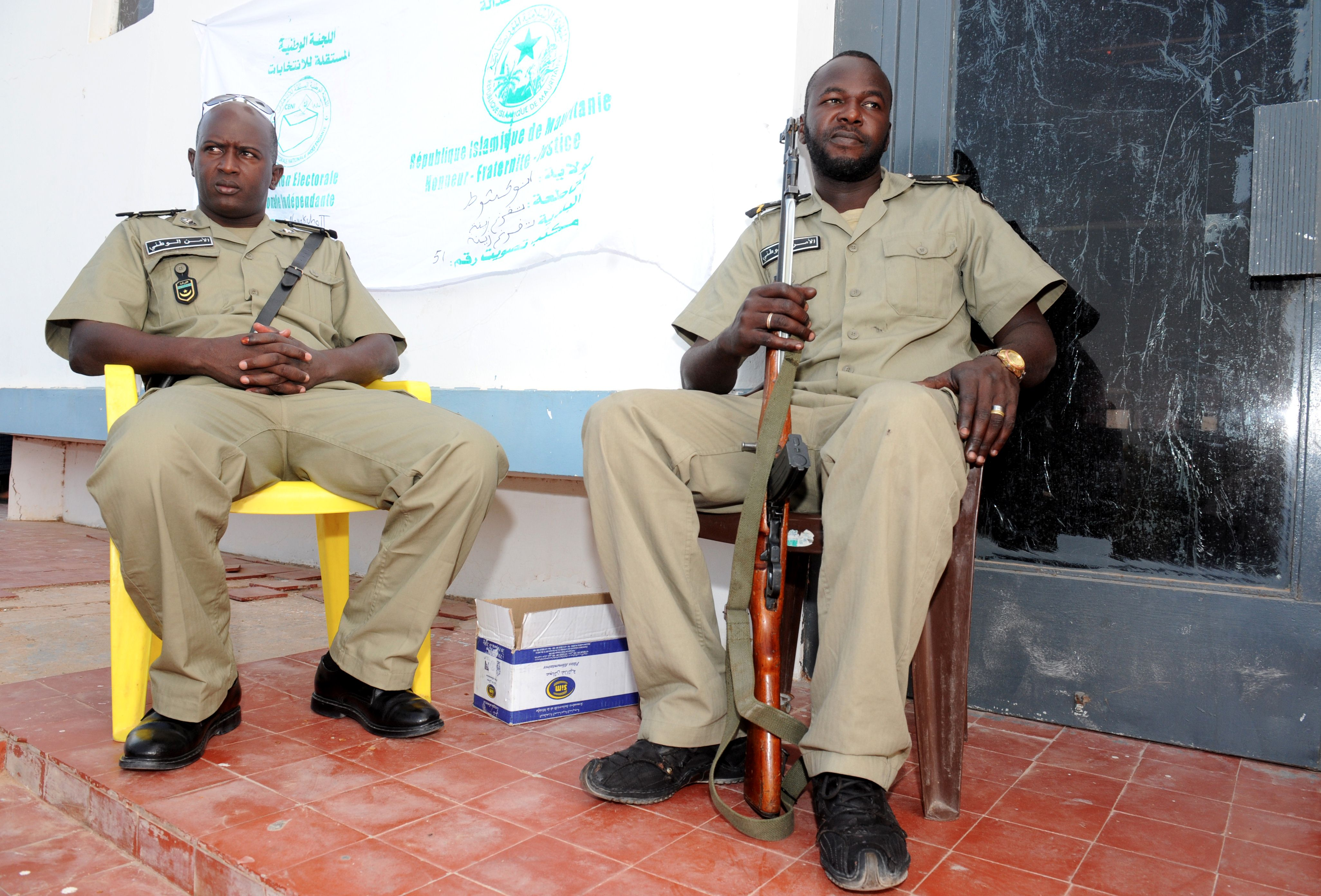 Mauritanian police officers stand guard outside a polling station in Nouakchott, on June 21, 2014, during the presidential elections. The Islamic Republic of Mauritania is led by Mohamed Ould Abdel Aziz, an ex-general who led a 2008 coup and won election a year later. He is tipped to win Saturday's presidential poll as leading opposition groups have vowed to boycott the ballot.  (AFP PHOTO / SEYLLOU)