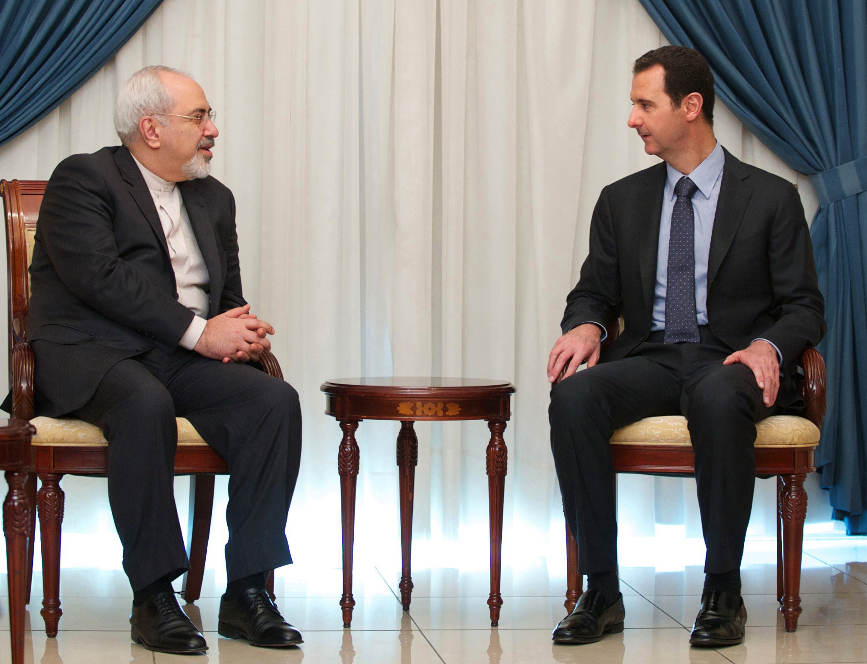"A handout picture released by the official Syrian Arab News Agency (SANA) on January 15, 2014 shows President Bashar al-Assad (R) meeting with Iranian Foreign Minister Mohammad Javad Zarif  in Damascus on January 15 , 2013.  Assad warned during the meeting that Saudi Arabia's political and religious ideology is ""a threat to the world,"" state television reported.   AFP PHOTO/ HO/ SANA   == RESTRICTED TO EDITORIAL USE - MANDATORY CREDIT  ""AFP PHOTO / HO / SANA"" - NO MARKETING NO ADVERTISING CAMPAIGNS - DISTRIBUTED AS A SERVICE TO CLIENTS ==CAMPAIGNS - DISTRIBUTED AS A SERVICE TO CLIENTS =="