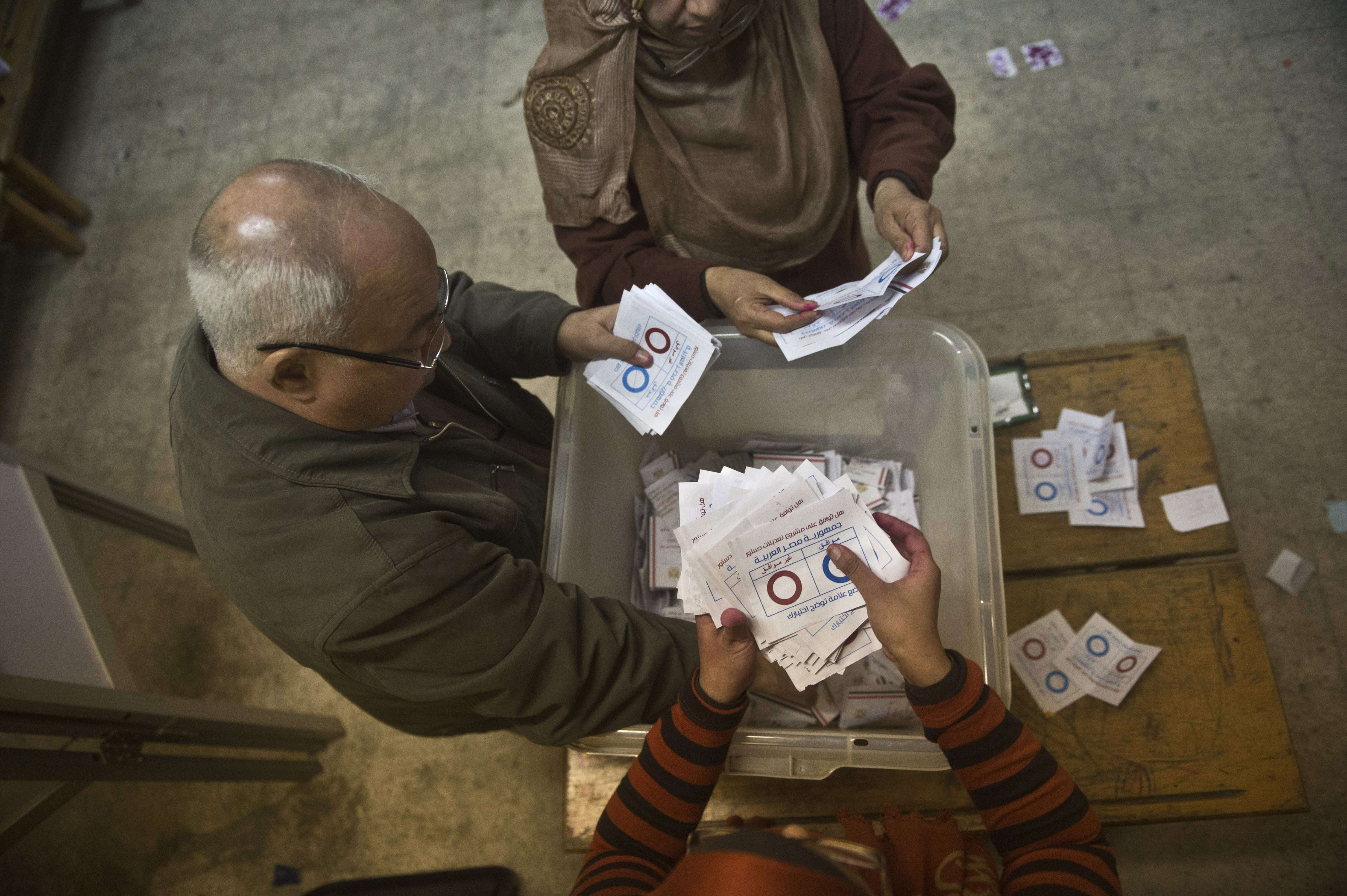 Polling station officials count ballots in Cairo on 15 January 2014 (AFP Photo)