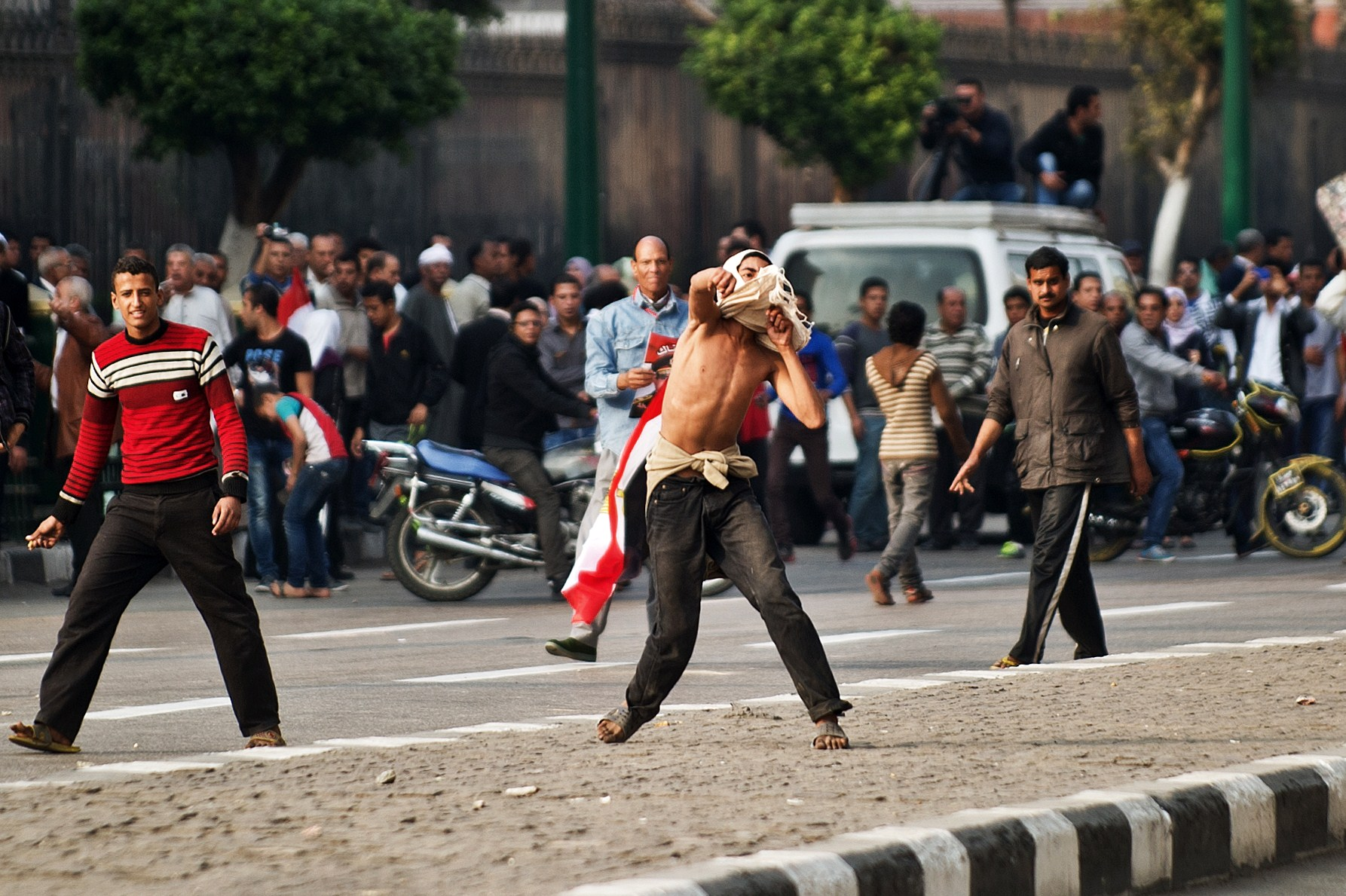 Egyptian supporters of the military regime throw stones towards anti-regime protesters (unseen) during clashes in Cairo's Tahrir Square on November 19, 2013 in Cairo, (AFP PHOTO/GIANLUIGI GUERCIA)