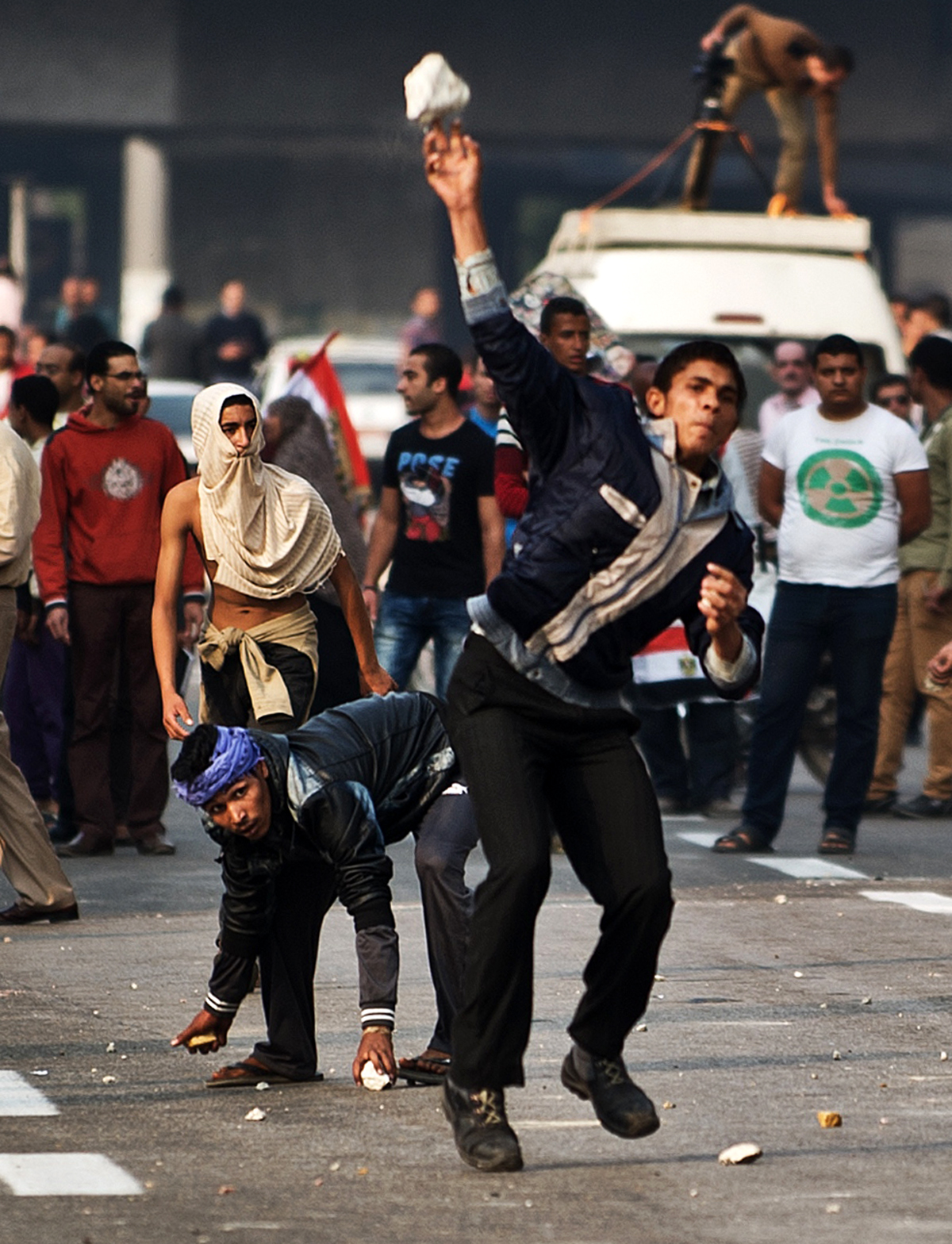 Egyptian supporters of the military regime throw stones towards anti-regime protesters (unseen) during clashes in Cairo's Tahrir Square on November 19, 2013 in Cairo, Egypt.  ( AFP PHOTO/GIANLUIGI GUERCIA)