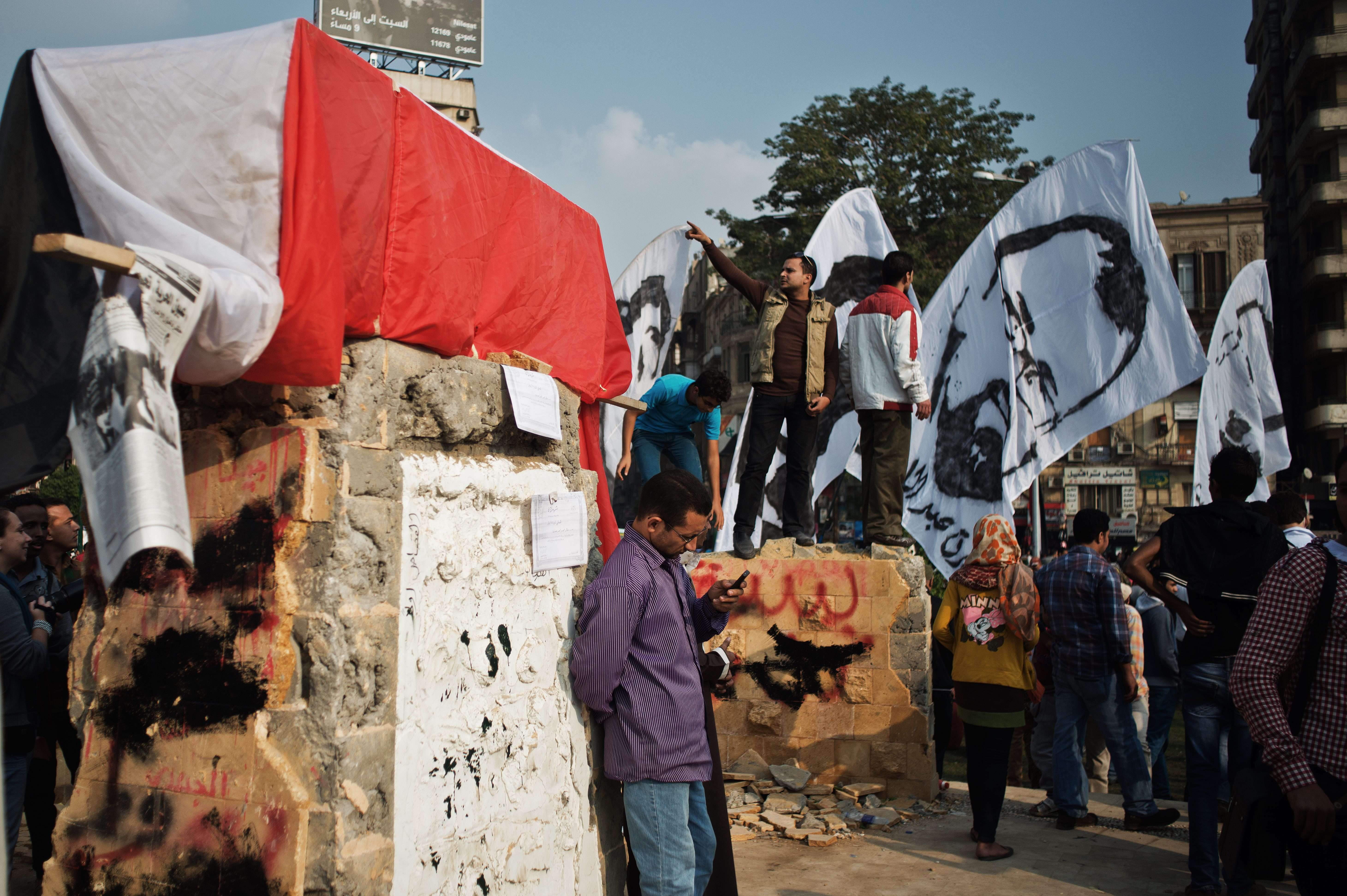 Egyptians gather near a memorial to those killed in Egypt's uprising that has a fake coffin on its top on November 19, 2013 in Tahrir square in Cairo as dozens of supporters and opponents of the army mark the anniversary of anti-military protests. (  AFP PHOTO/GIANLUIGI GUERCIA)