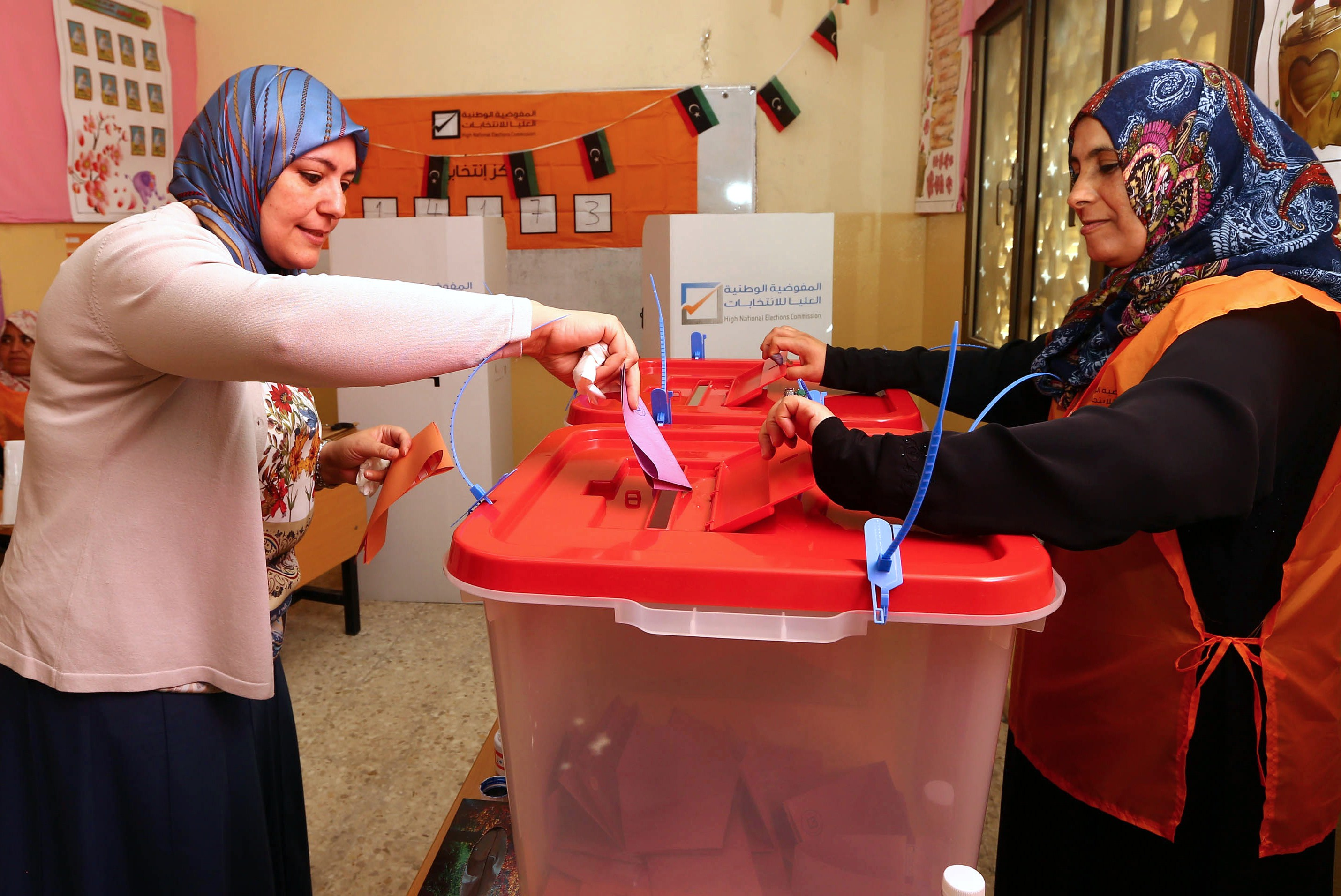 A Libyan woman casts her ballot at a polling station during legislative elections in the capital Tripoli on June 25, 2014. Polling was under way across Libya in a general election seen as crucial for the future of a country hit by months of political chaos and growing unrest. Voters are choosing from among 1,628 candidates, with 32 seats in the 200-strong General National Congress reserved for women and would-be MPs banned from belonging to any political party.   (AFP PHOTO/MAHMUD TURKIA)