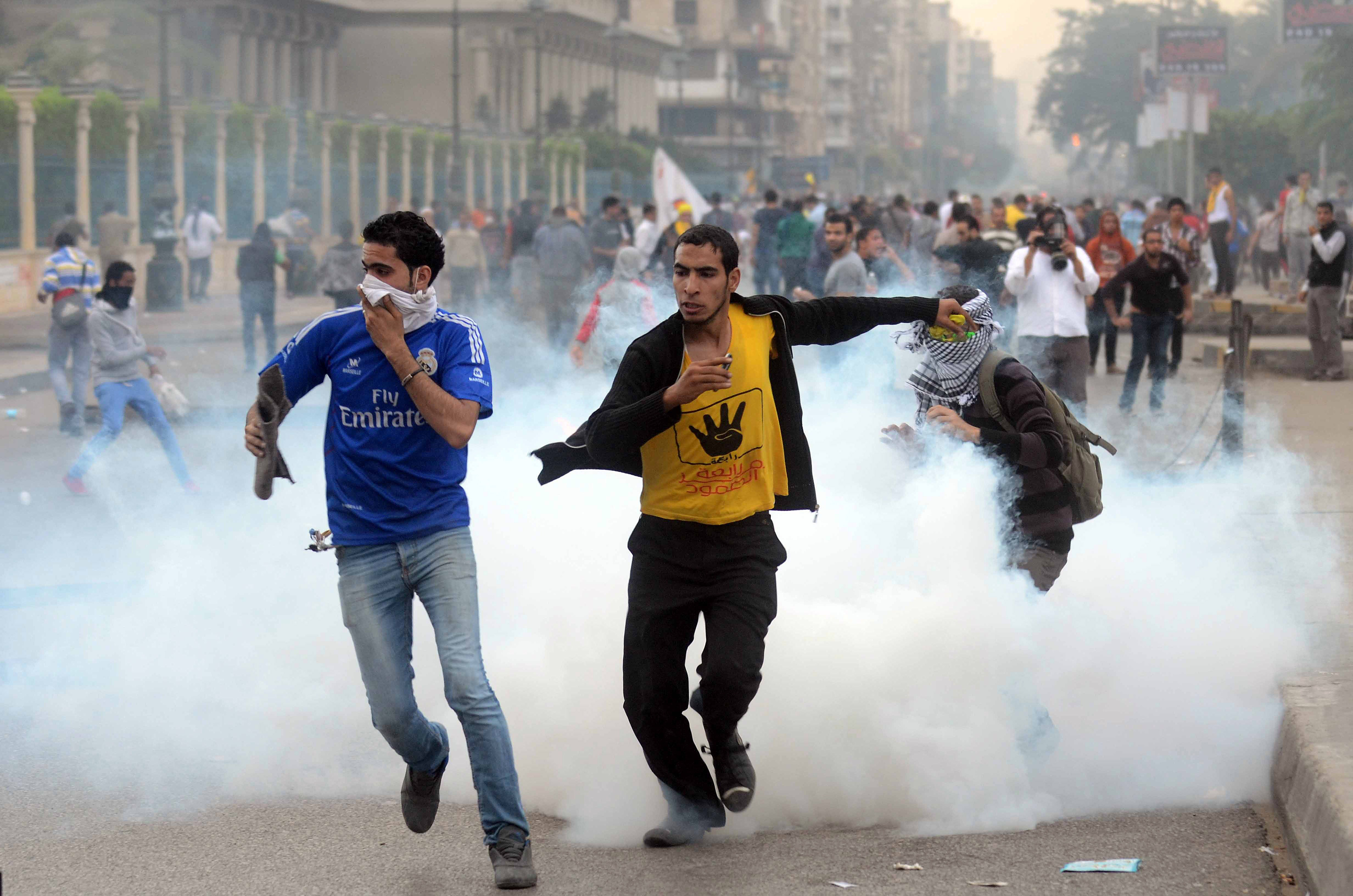 Supporters of ousted president Mohamed Morsi and the Muslim brotherhood run away from tear gas during clashes with Egyptian riot police close to Rabaa al-Adawiya square on November 22, 2013.  (AFP PHOTO/MOHAMED EL-SHAHED)