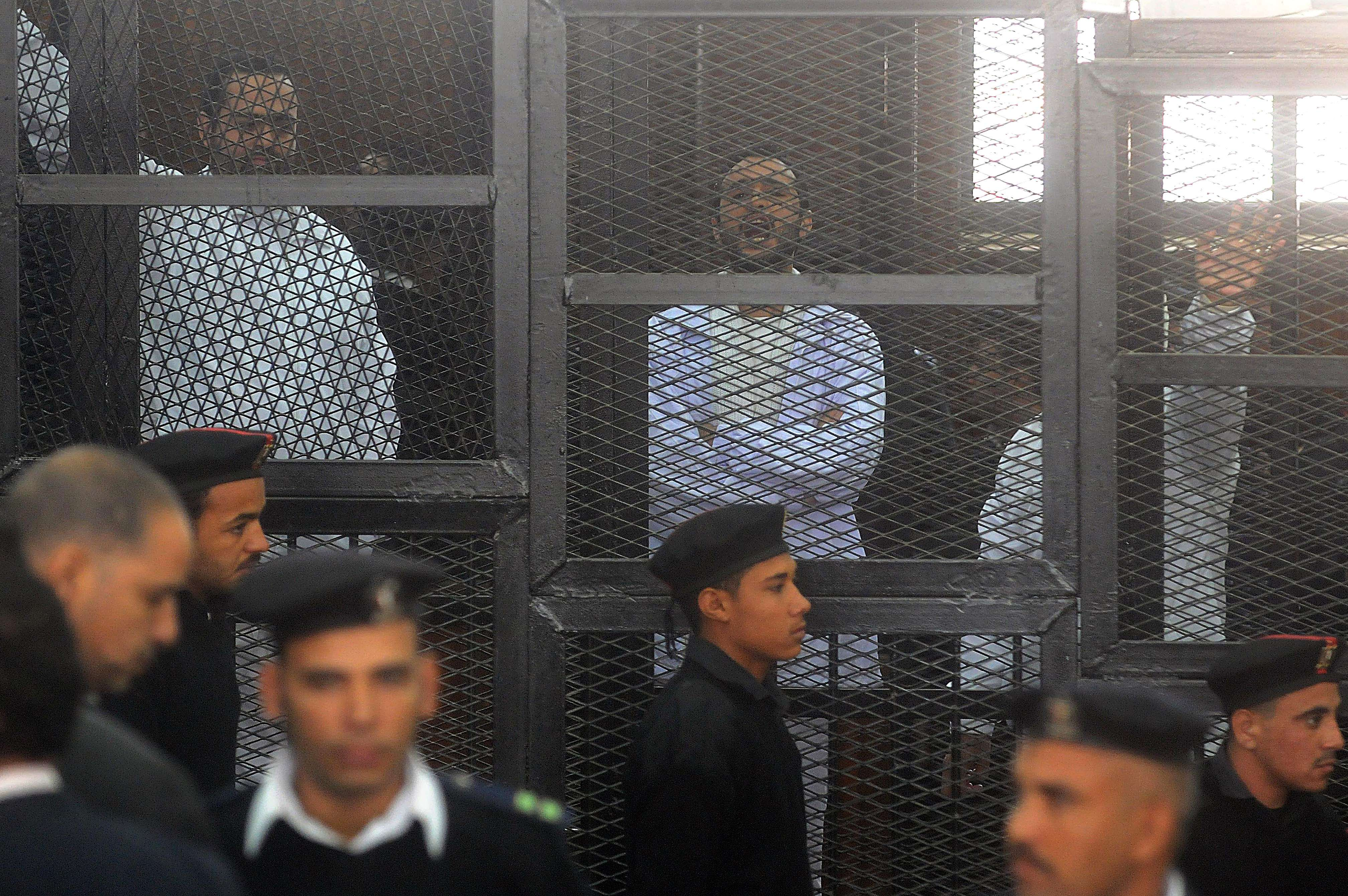 Egyptian activicts Mohamed Adel (L), Ahmed Douma (C) and Ahmed Maher (R) stand in the accused dock during their trial on December 22, 2013 in the capital Cairo. An Egyptian court sentenced three activists who spearheaded the 2011 uprising against Hosni Mubarak to three years in jail for organising an unlicensed protest, judicial sources said. It was the first such verdict against non-Islamist protesters since the overthrow of president Mohamed Morsi in July, and was seen by rights groups as part of a widening crackdown on demonstrations by military-installed authorities.  (AFP PHOTO/STR)