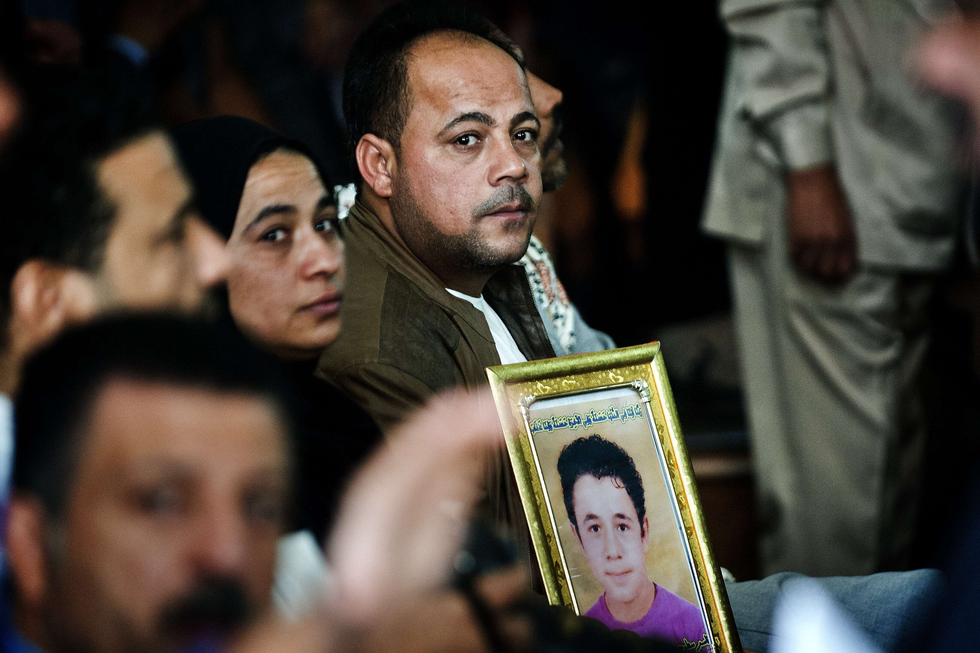 Setohy Abdel Rahman holds a portrait of his son Ahmed, killed during early July clashes, outside the Muslim Brotherhood headquarters, during the second trial hearing for Muslim Brotherhood supreme leader Mohammed Badie and his aides on October Tuesday.  (AFP PHOTO/GIANLUIGI GUERCIA)