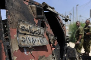 Israeli soldiers inspect a burnt armoured vehicle near the Kerem Shalom border crossing after unidentified gunmen crossed into Israel from Egypt on 6 August. The number plate reads 'Border Guards Forces'