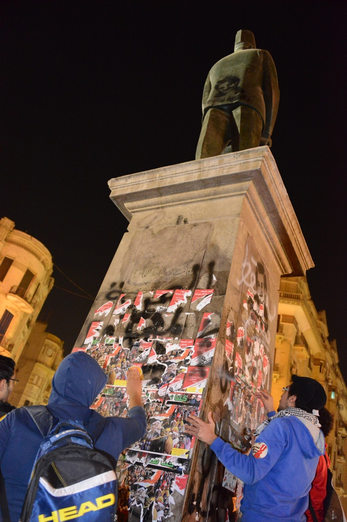 "During a march by the Revolutionary Front on Monday night, protestors in Talaat Harb Square tear down stickers on a statue supporting commander of the military Abdel Fatah Al-Sisi and urging Egyptians to vote ""yes"" in the constitutional referendum  Aaron T. Rose"