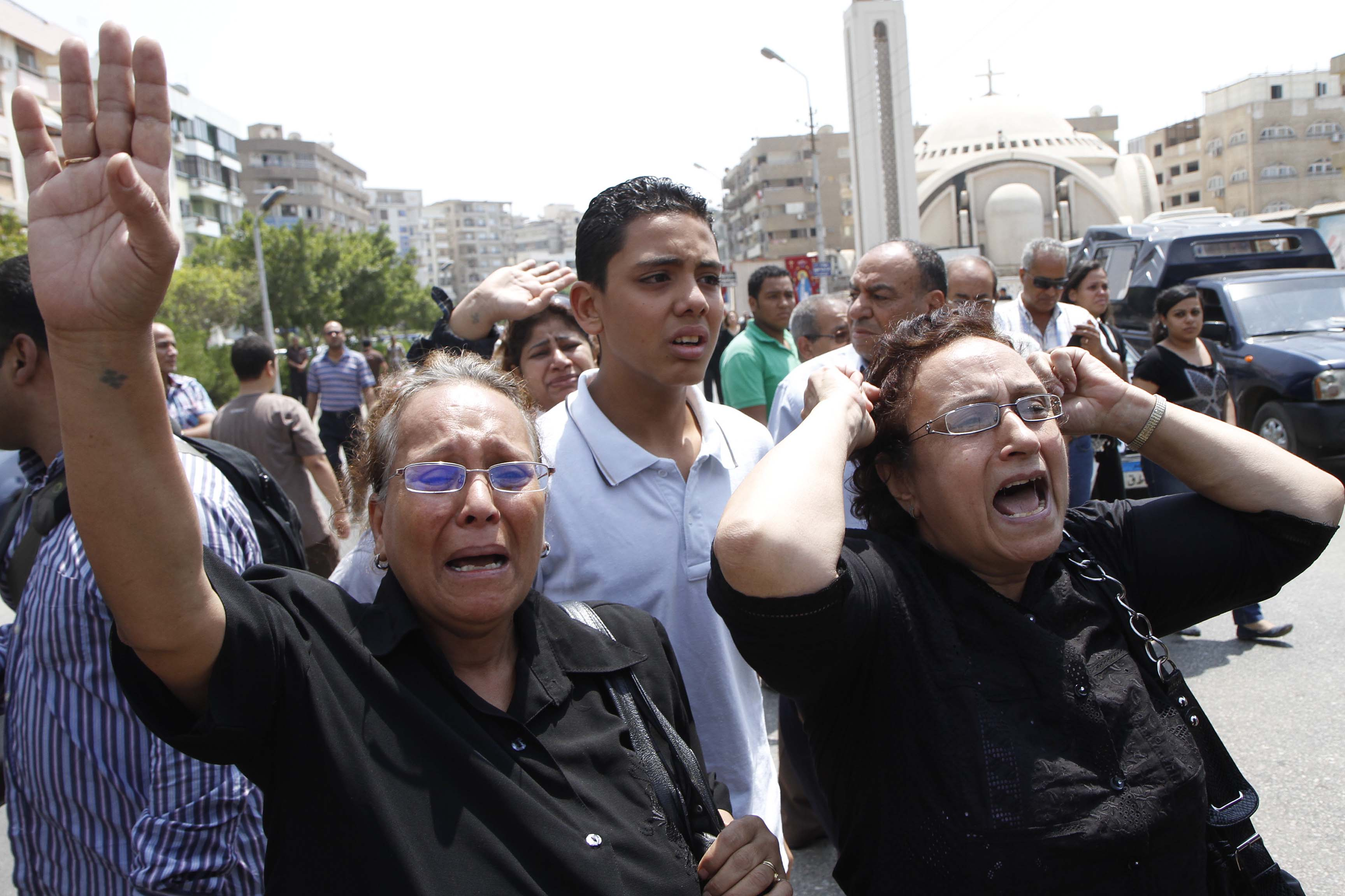 Egyptian relatives of supporters of ousted Islamist president Mohamed Morsi cry sitting outside the courthouse on Monday in Minya, after the court ordered the execution of 529 Morsi supporters after only two hearings (AFP PHOTO )