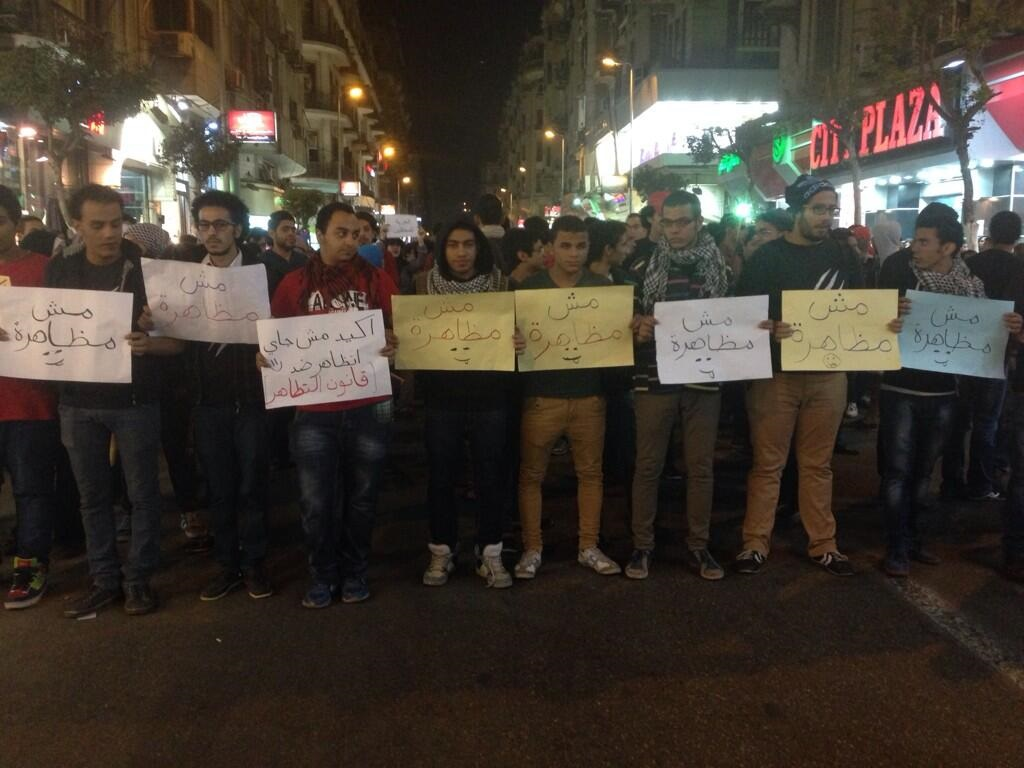 "Protesters hold signs reading ""this is not a protest"" in defiance to the Protest Law during a demonstration in Talaat Harb square Saturday night (Photo by Fady Ashraf)"