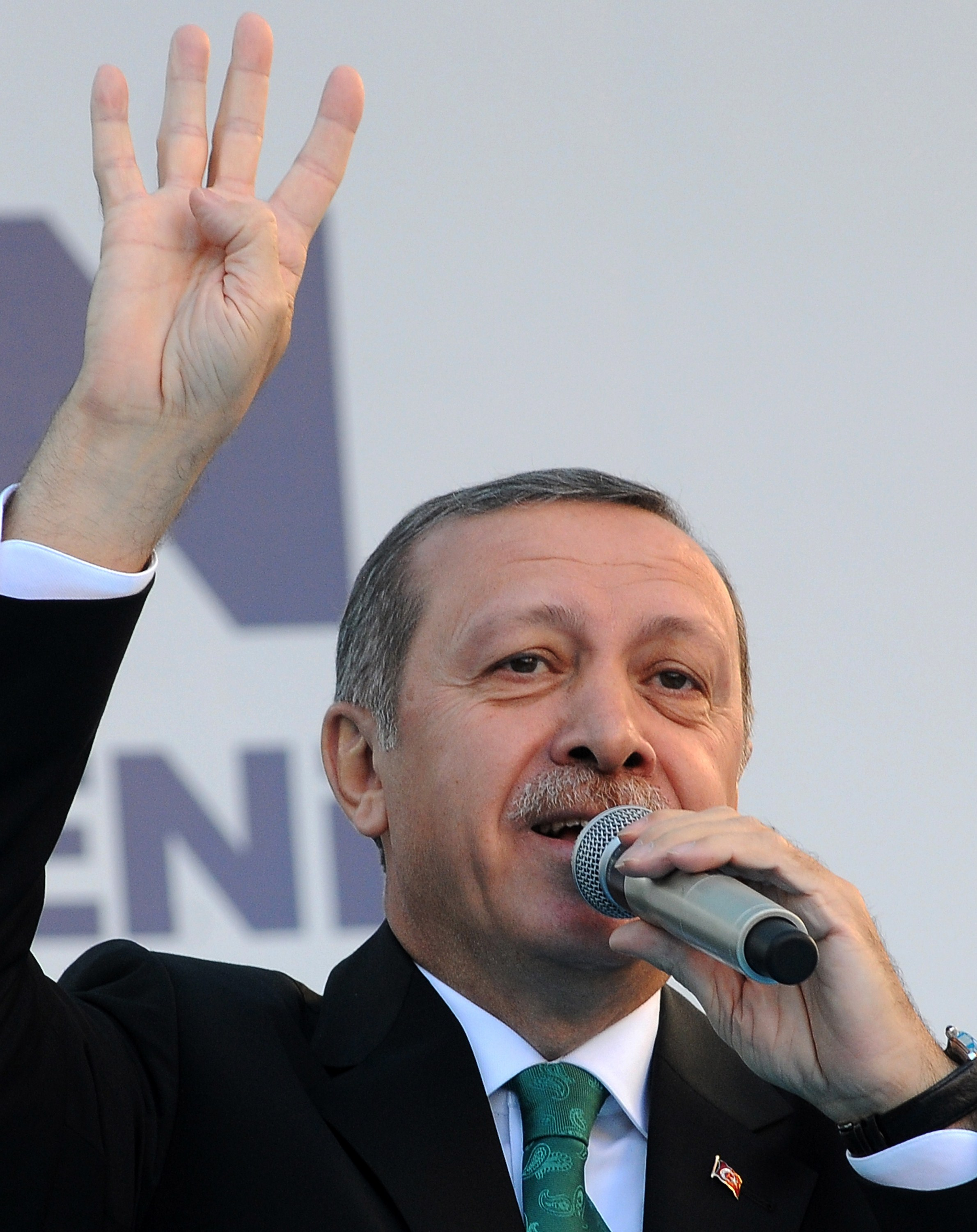 "Turkish Prime Minister Recep Tayyip Erdogan gestures the four-finger salute used by supporters of ousted Egyptian president Mohamed Morsi, a symbol known as ""Rabaa"", which means four in Arabic, remembering those killed in the crackdown on the Rabaa al-Adawiya protest camp in Cairo in early 2013, as he delivers a speech in Trabzon on November 23, 2013. Turkey declared Egypt's ambassador ""persona non grata"" and downgraded diplomatic relations to the level of charge d'affaires on November 23, in a tit-for-tat move after Cairo expelled its envoy, the foreign ministry said in a statement. Erdogan said his government would never respect military-installed rulers, in remarks made after Egypt's expulsion of Ankara's ambassador.    (AFP PHOTO/STRINGER)"