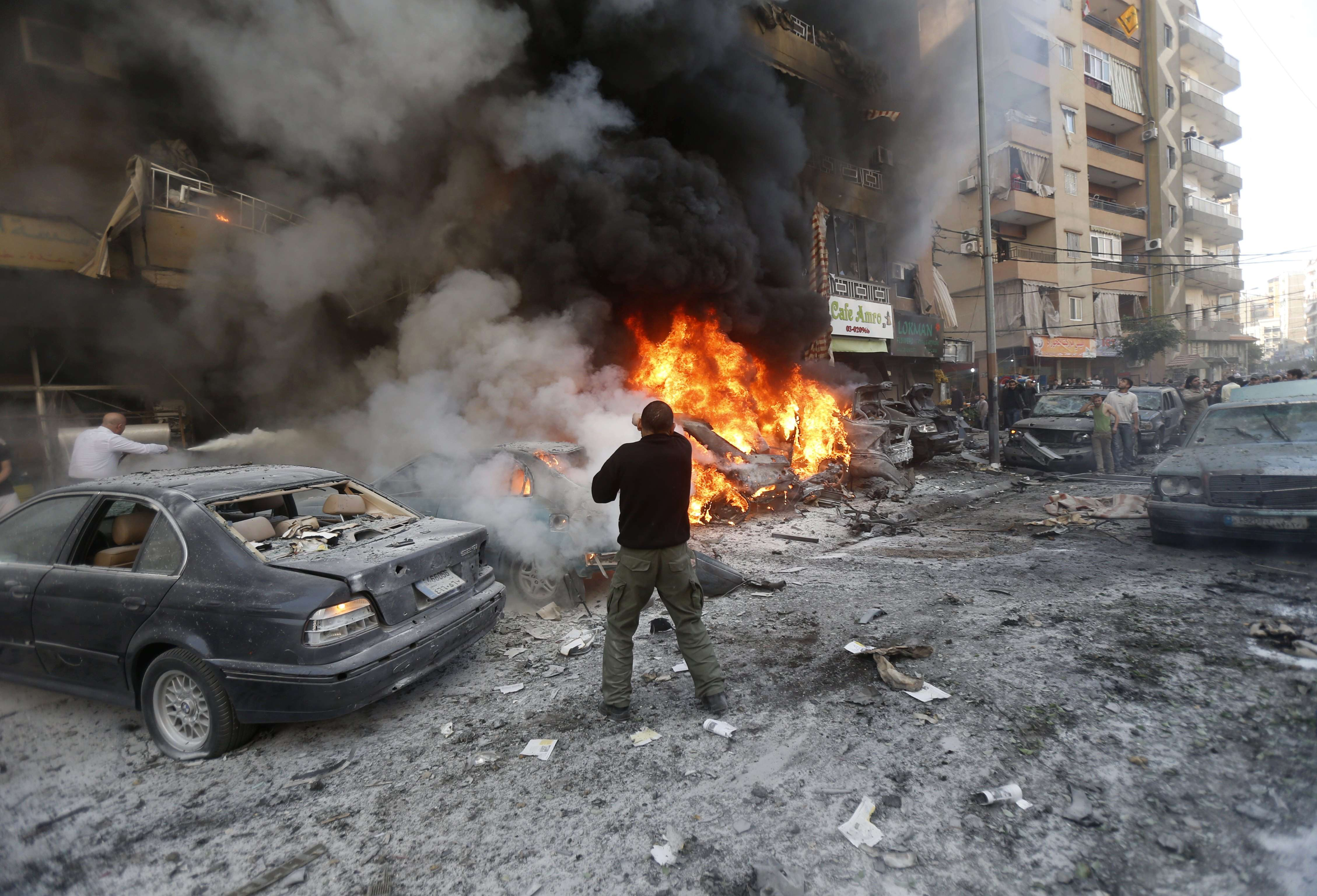 Lebanese men try to extinguish fire from burning cars following an explosion on January 21, 2014 in Haret Hreik, a south Beirut neighbourhood considered a stronghold of the Lebanese Shiite movement Hezbollah. Two people were killed in the apparent suicide car bombing, Lebanon's National News Agency said. (AFP PHOTO/STR)